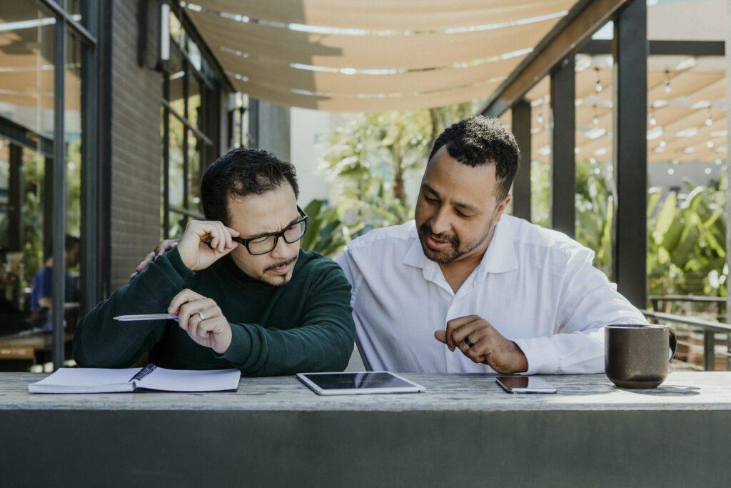 dos hombres viendo un iPad, y pensando como se pueden convertir en un líder de opinión en línea