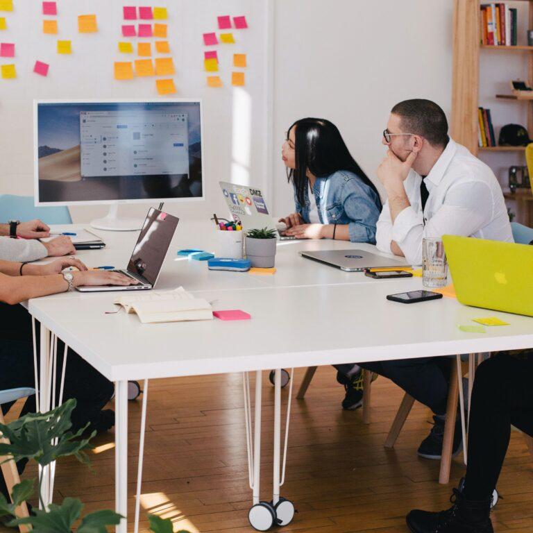 Personas en una oficina, representando a los empleados de una empresa cuando se reunen.