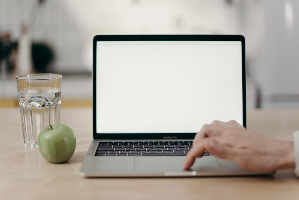 Laptop on desk next to a glass of water and an apple.