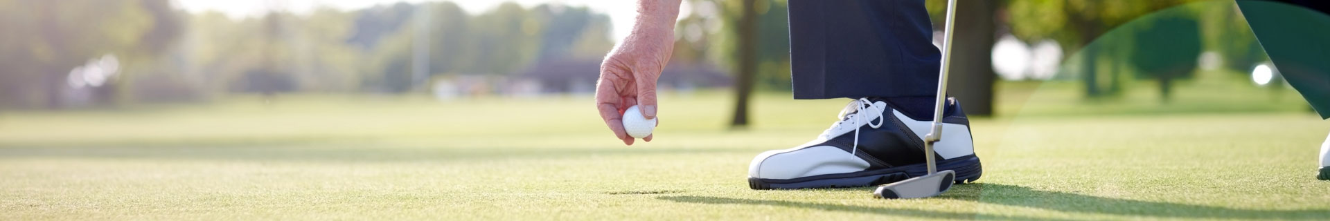 man places golf ball on the green to putt
