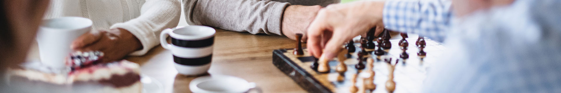 seniors play chess at the table while drinking coffee