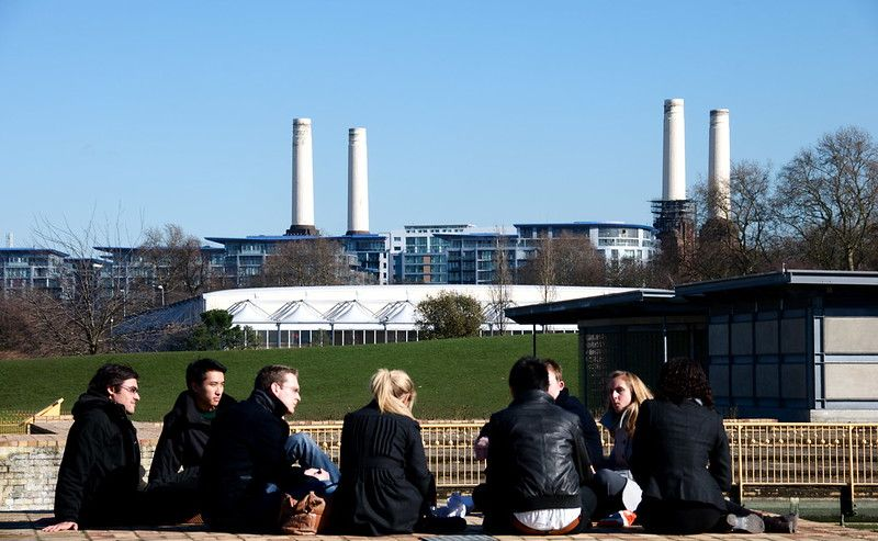 Some people gathering in a park with a power station in the     background.jpg