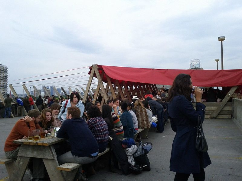 A rooftop cafe with many people sitting along a long table.jpg