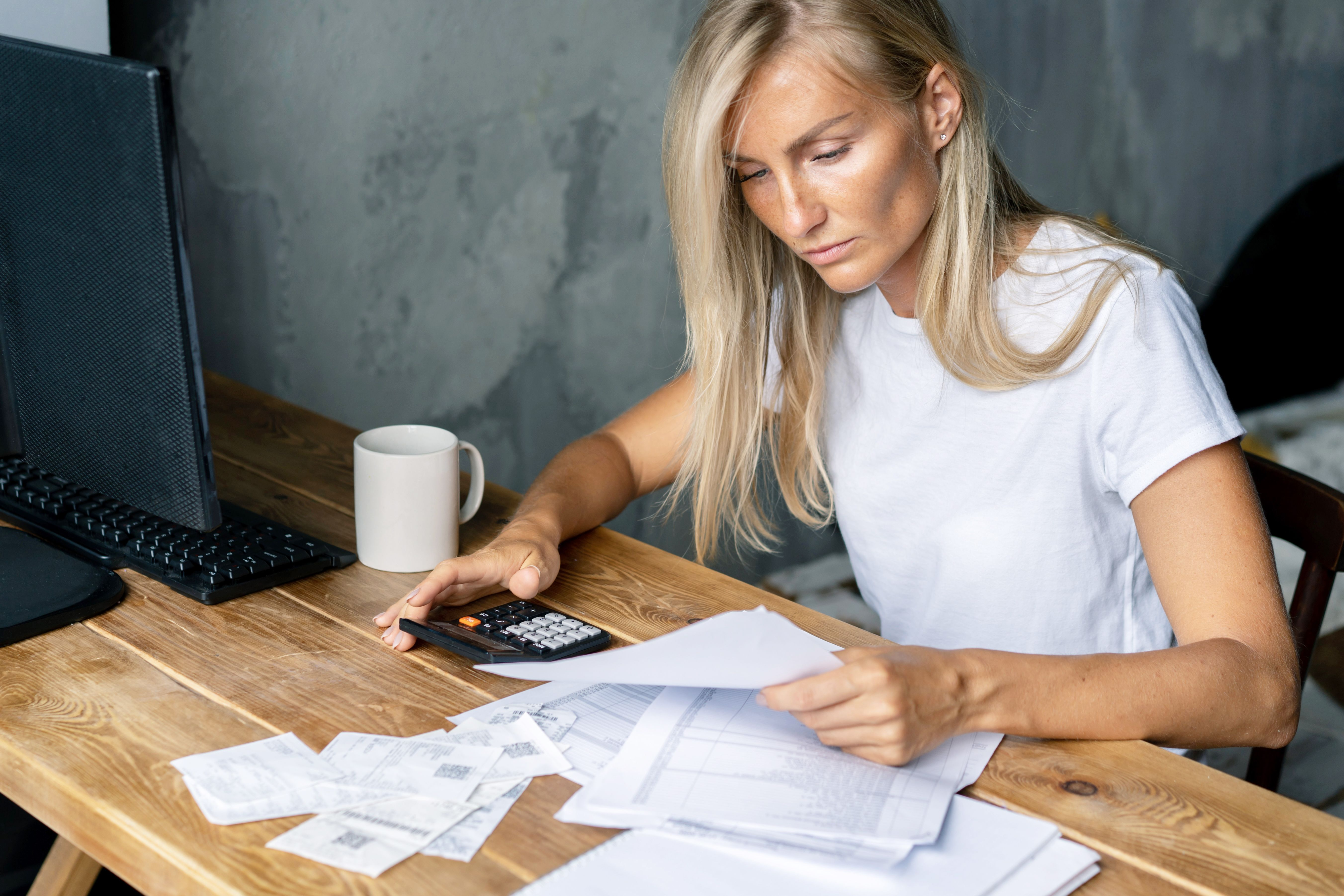 A blonde woman sits at a desk and works with bills and documents using a calculator