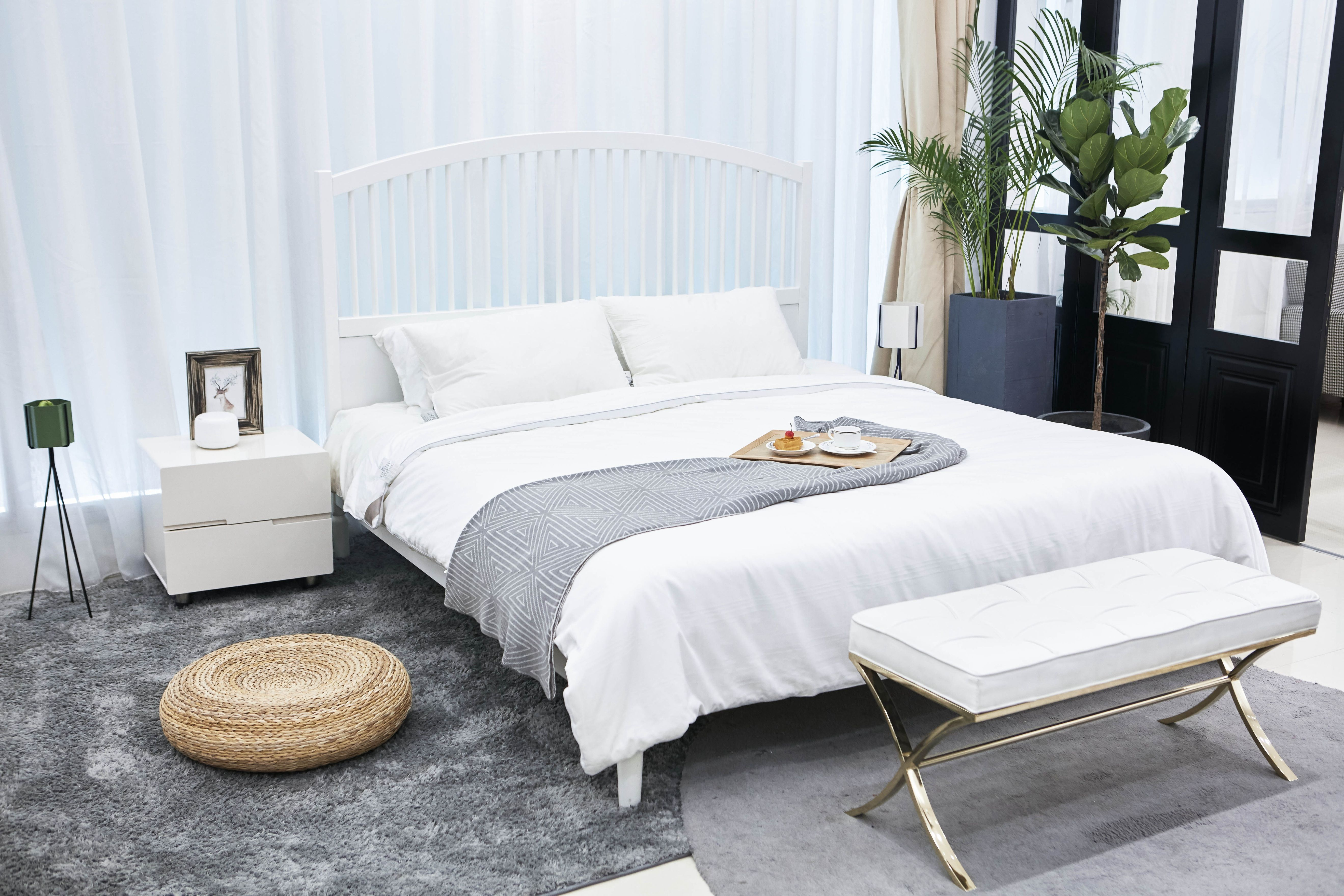 A king-size bed next to a white chest of drawers, a white bench and 2 green plants next to the balcony in a Build To Rent bedroom.