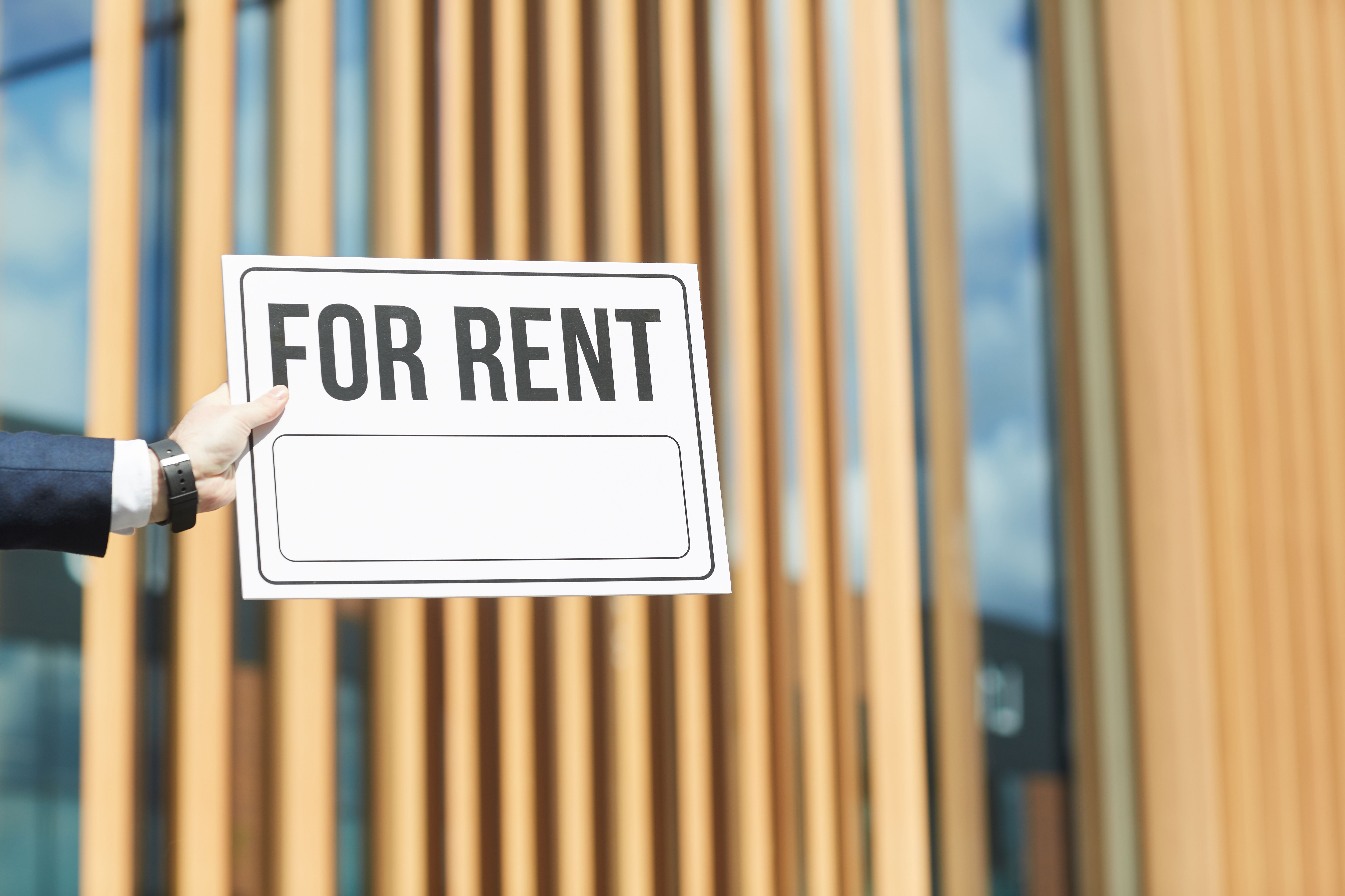 "Close-up of a man holding placard ""For Rent"" against a building"