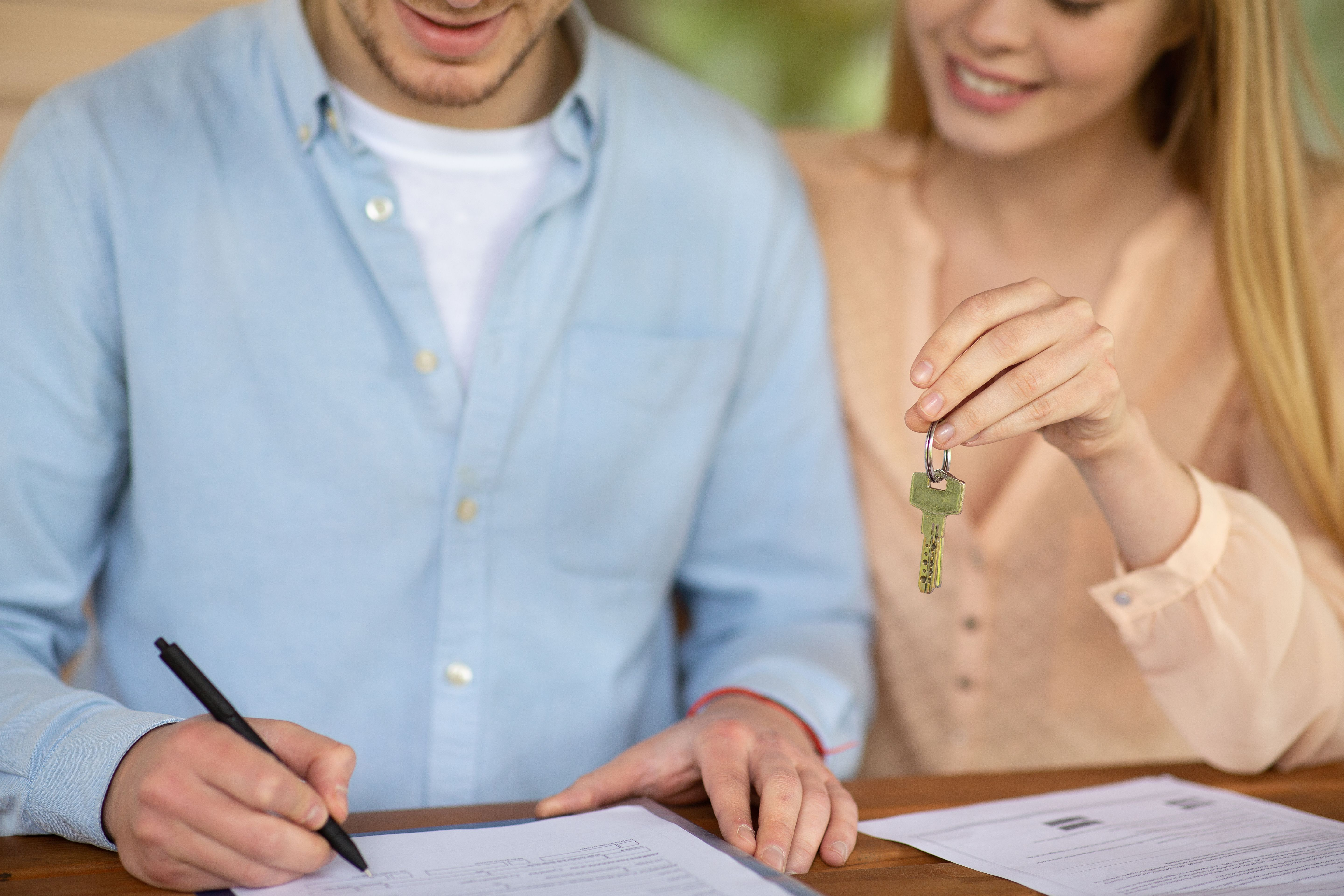 Closeup of a millennial couple signing a tenancy agreement while holding the keys to their new home