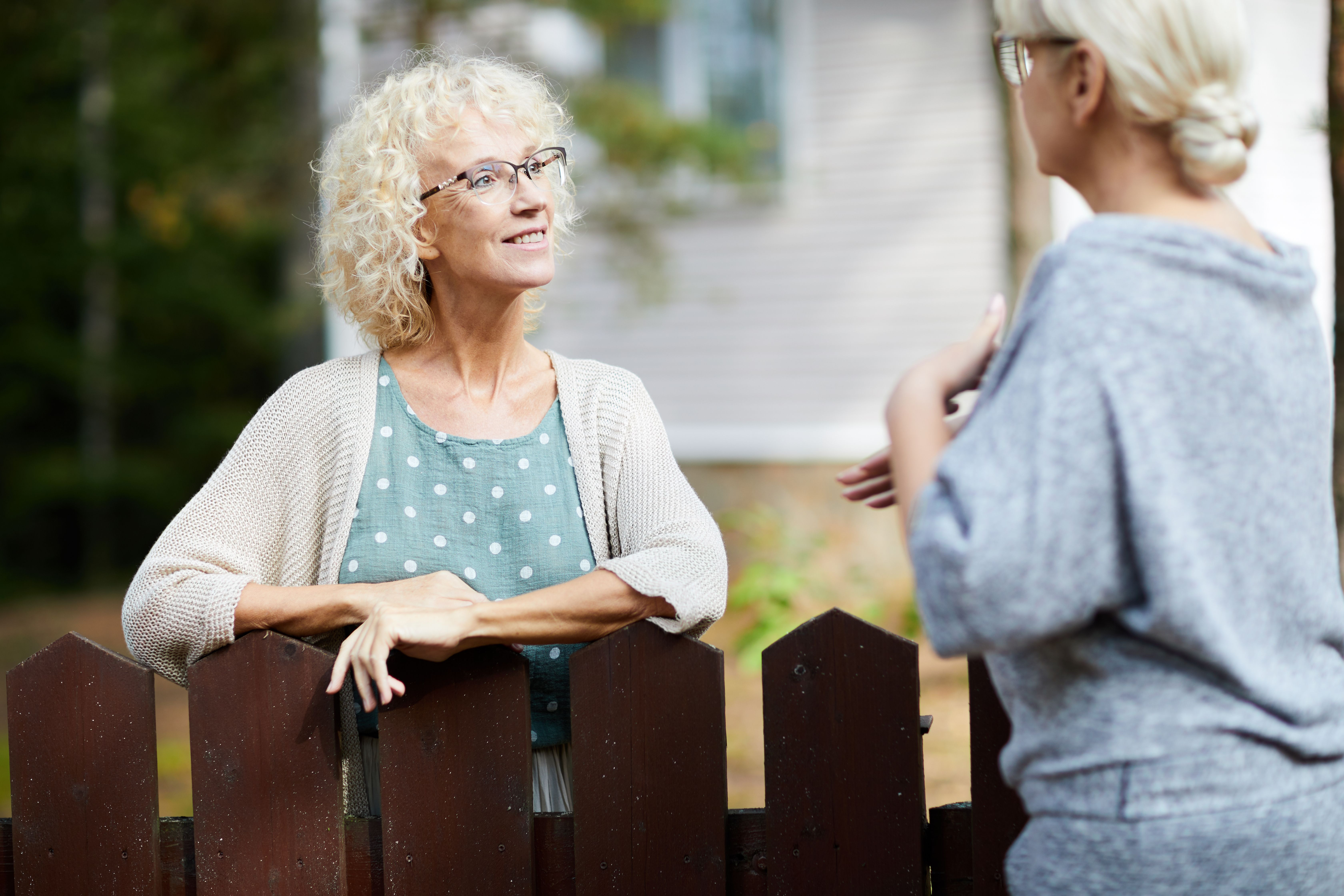 Two mature female neighbours talking through a fence
