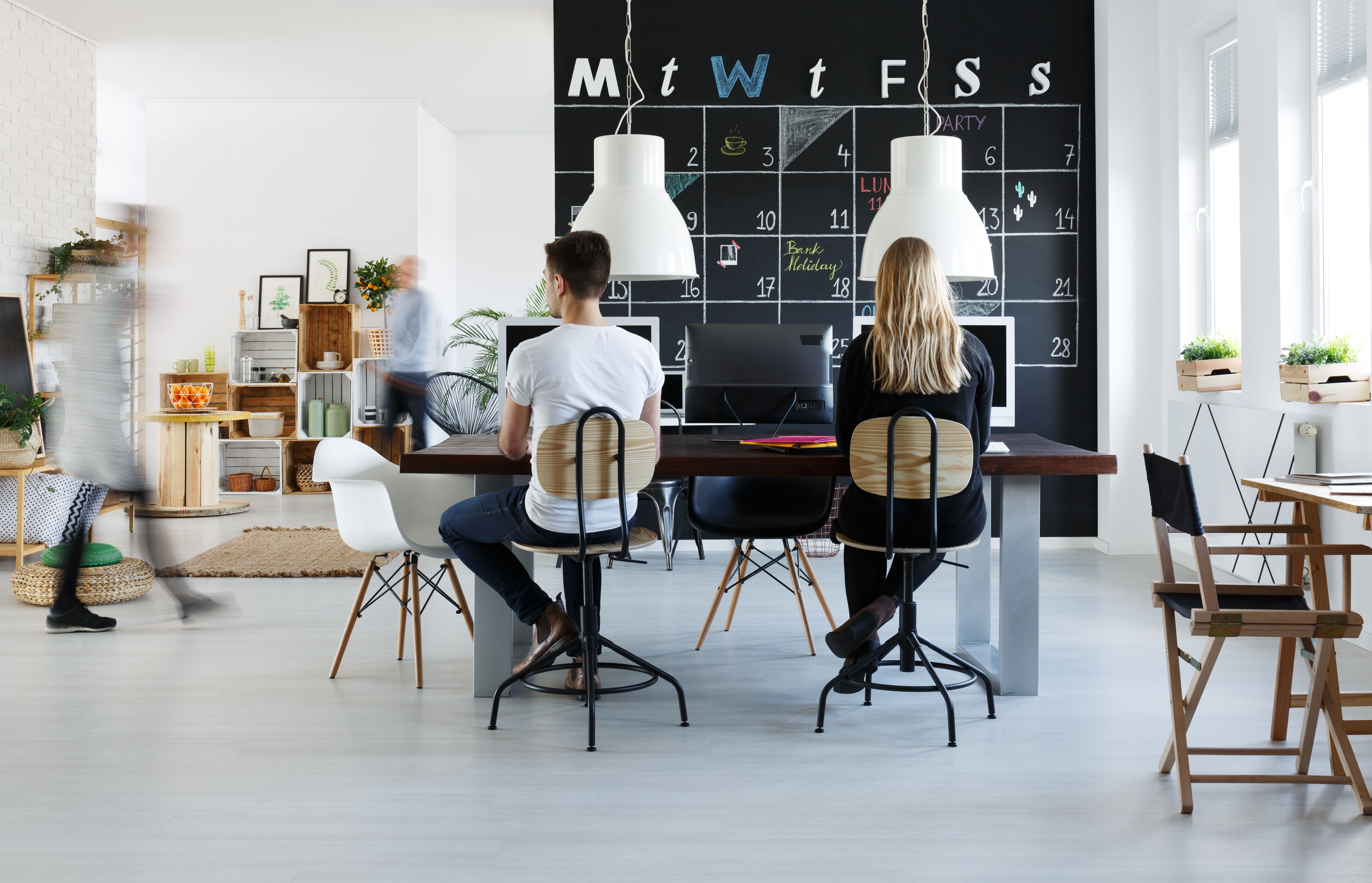 Freelancers in a co-working space with desks, chairs, plants and a calendar on the wall