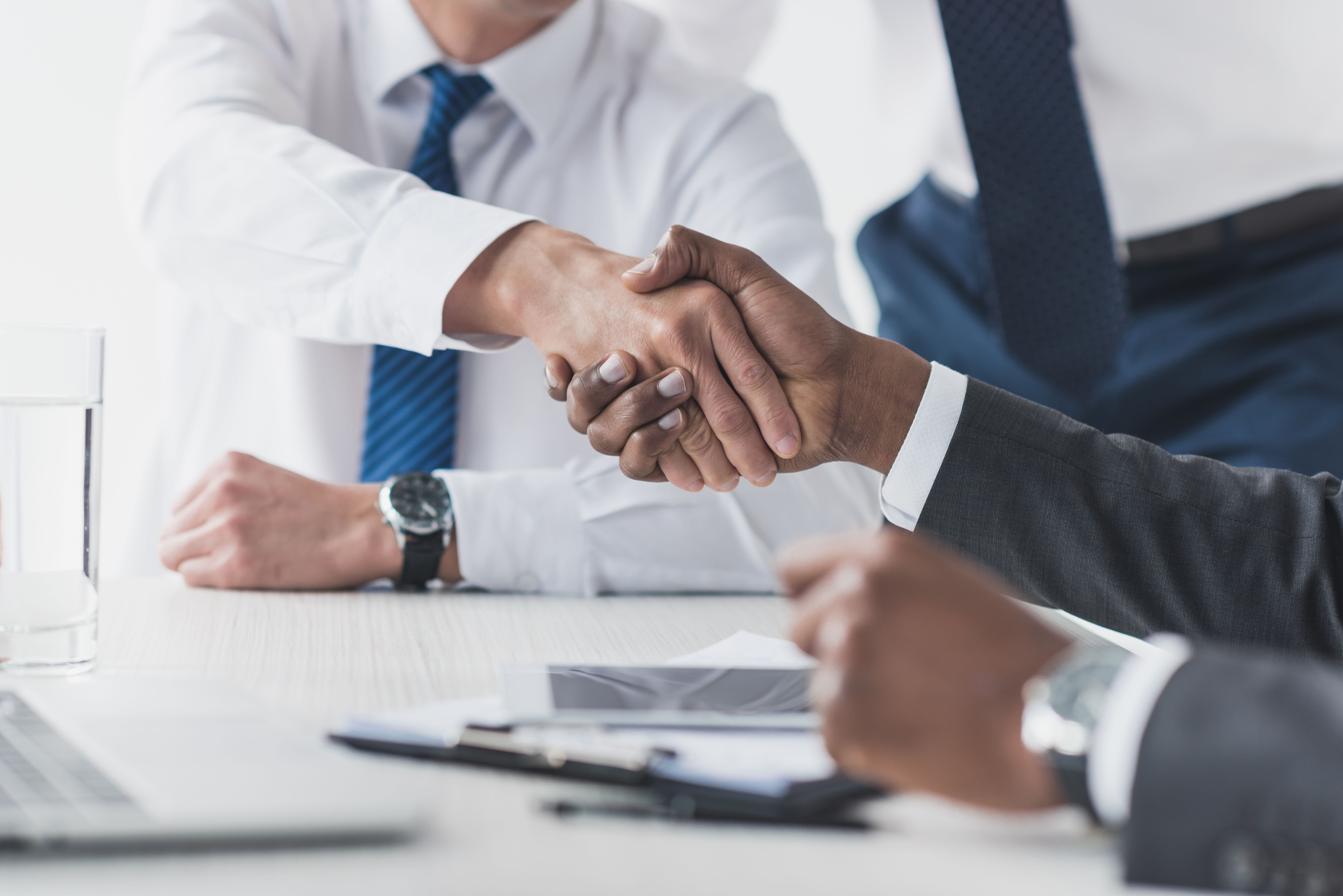 cropped shot of multicultural businessmen shaking hands while signing a contract in the workplace