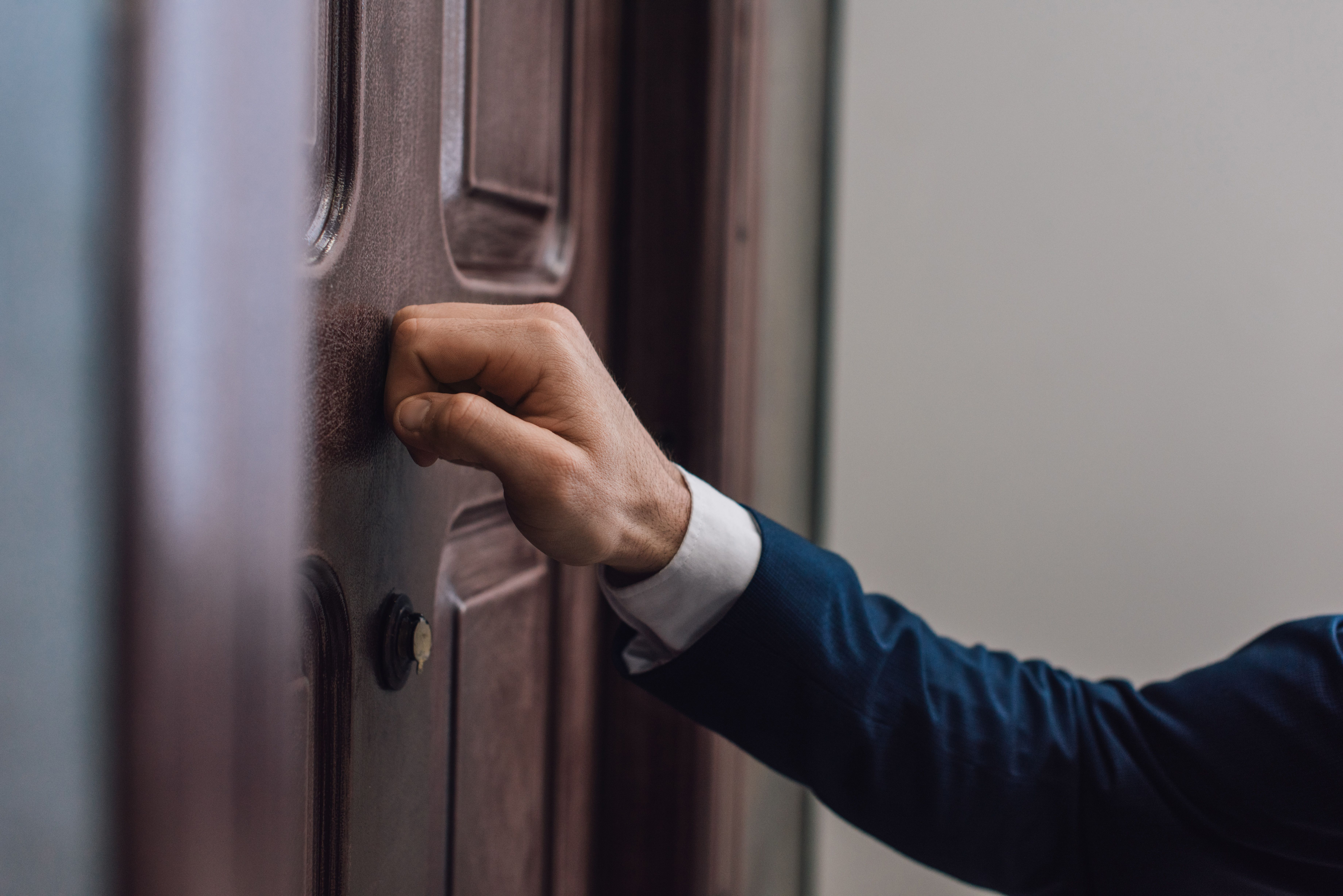 A men knocking on a door with his hand