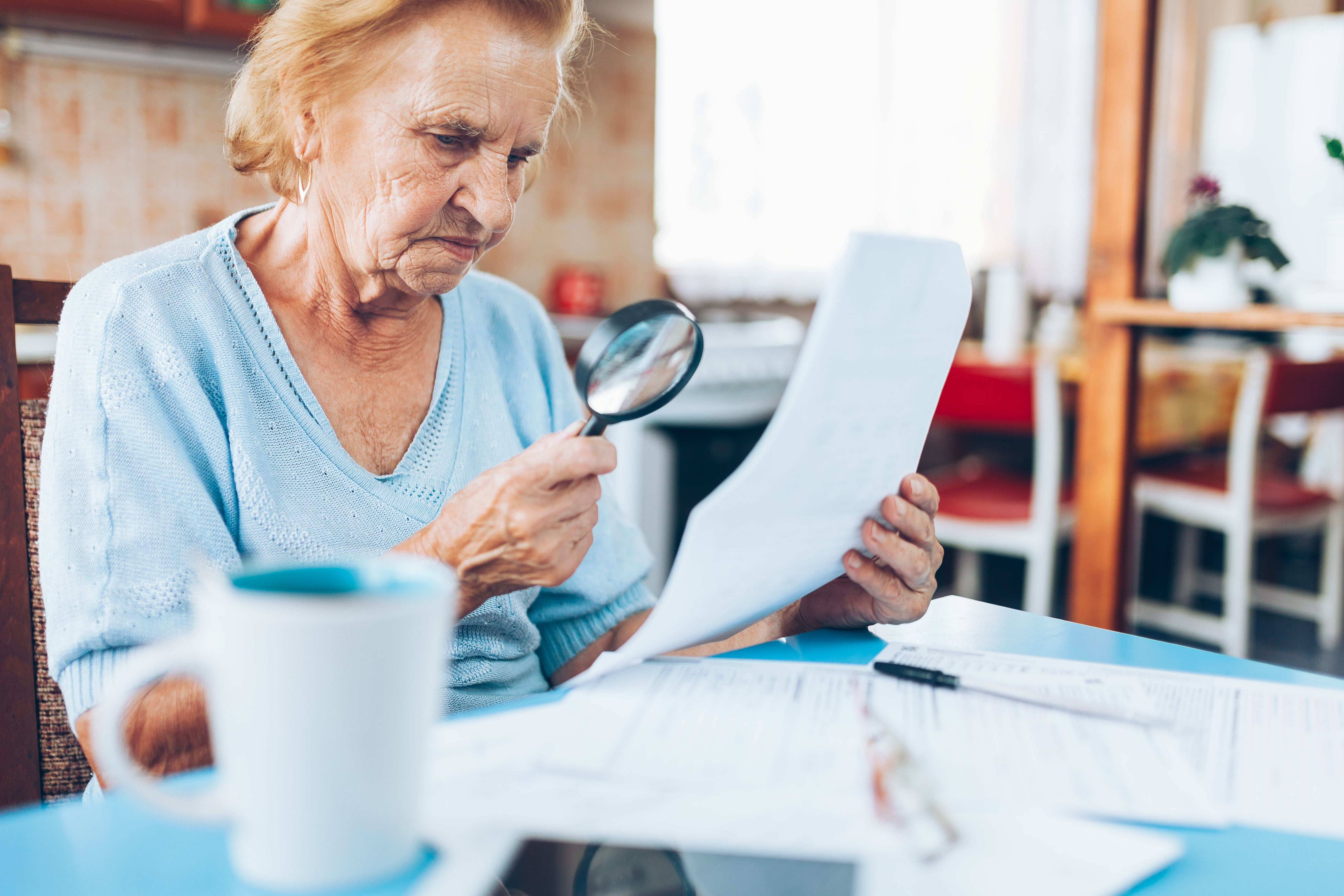 An elderly woman looking at her utility bills