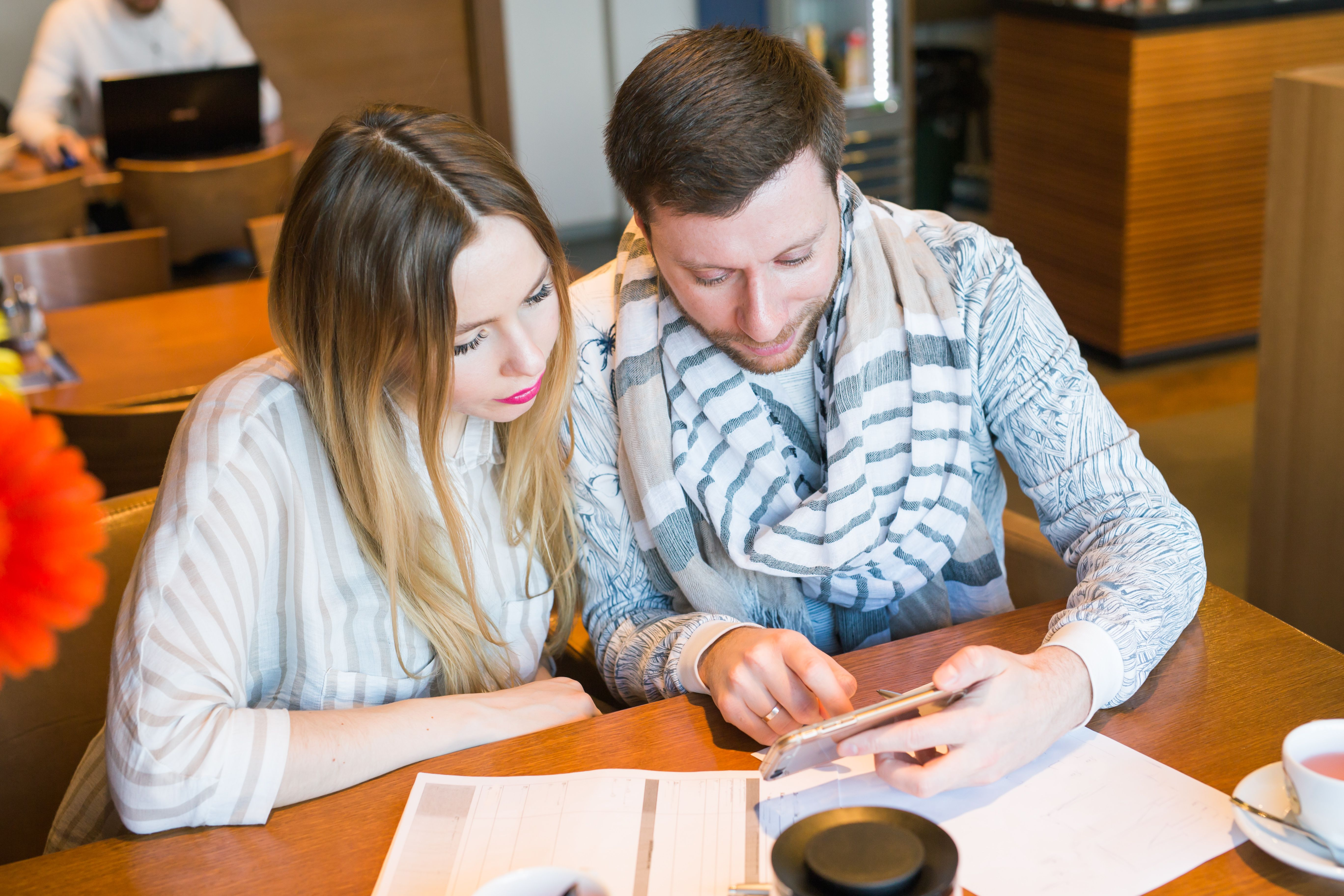 A man and a woman looking at a phone with documents and a coffee cup on their table