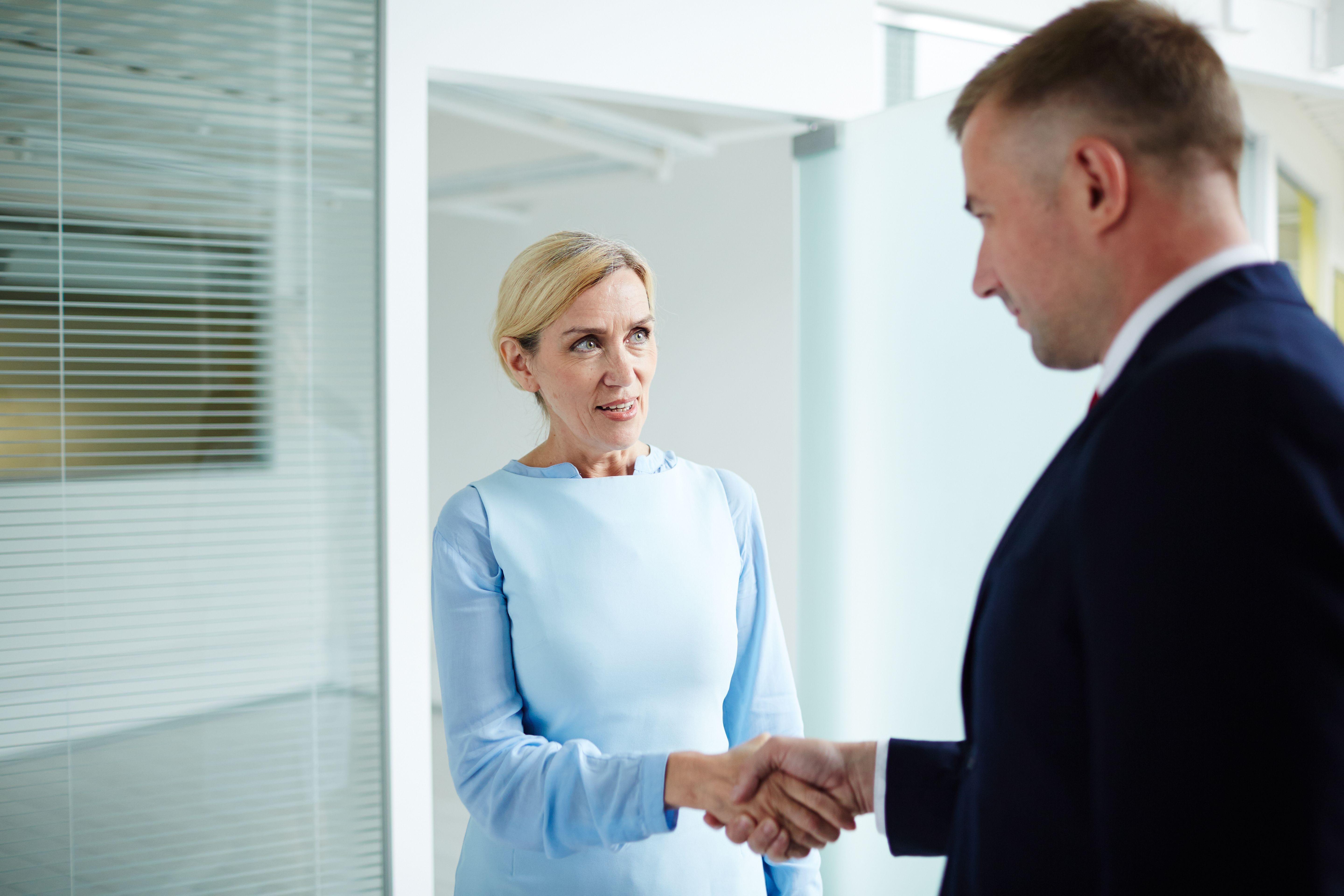 A man in suit shaking hand with a woman