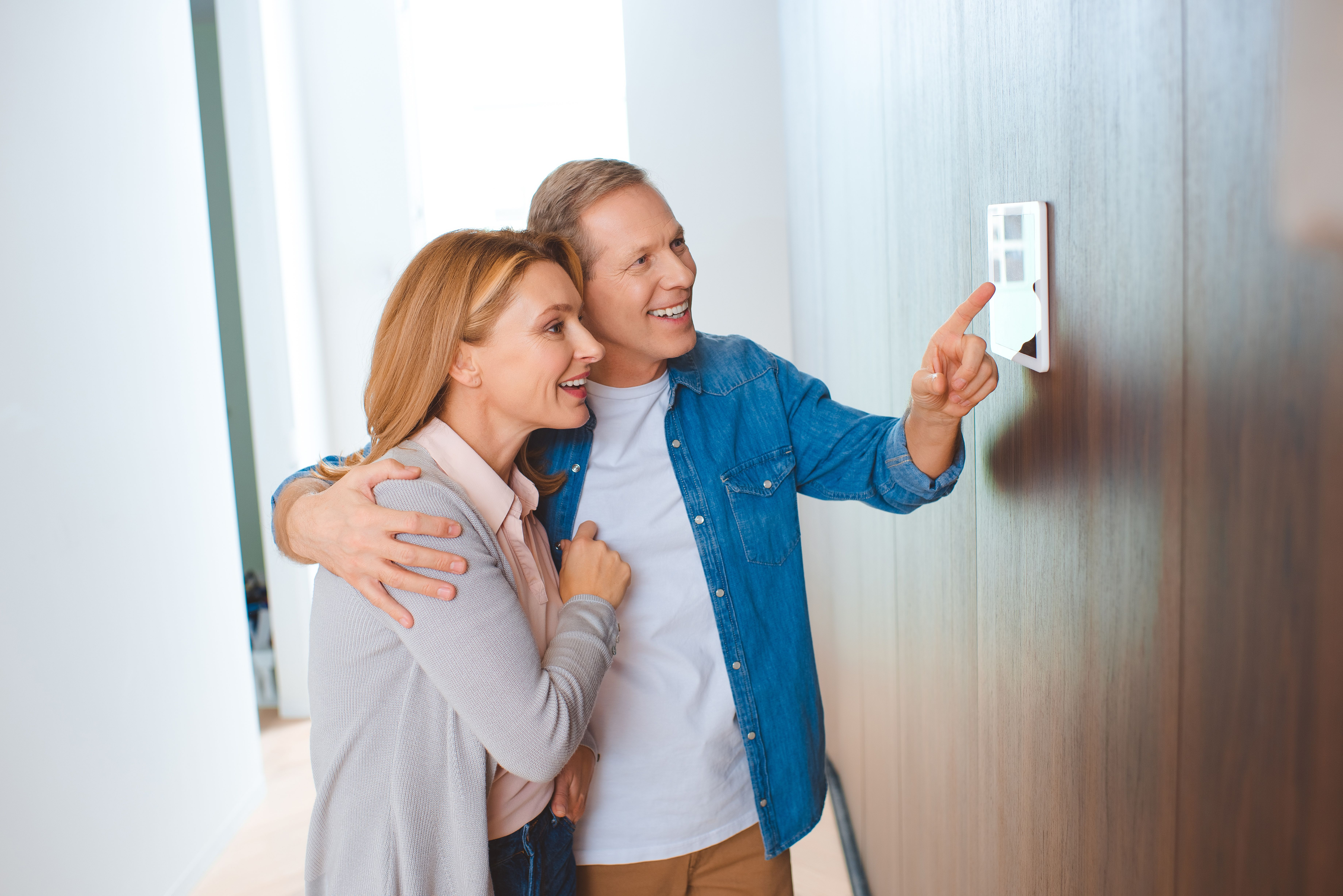 happy man pointing at heating control panel.jpg