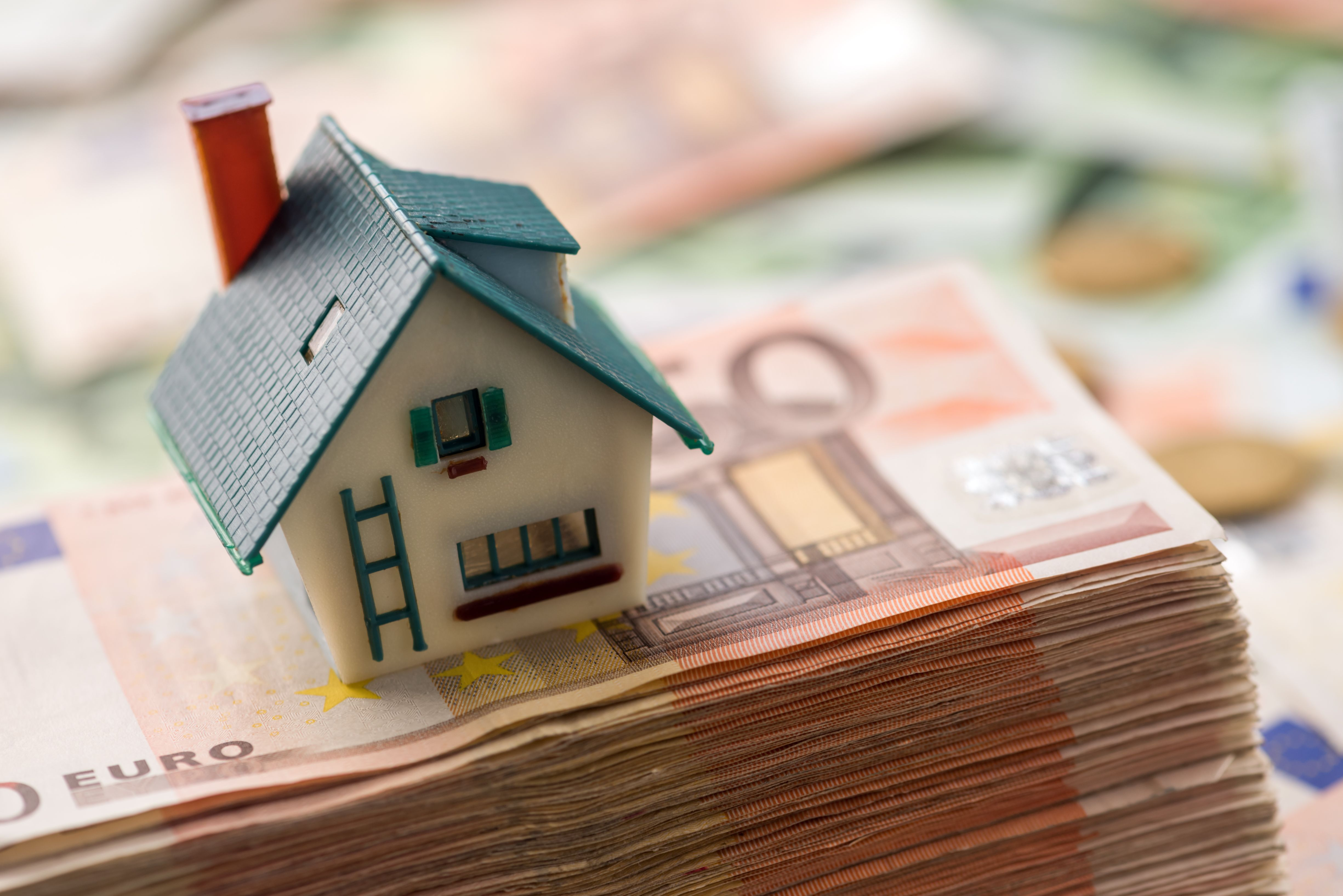 A pile of money with a model house on top against a blurred background