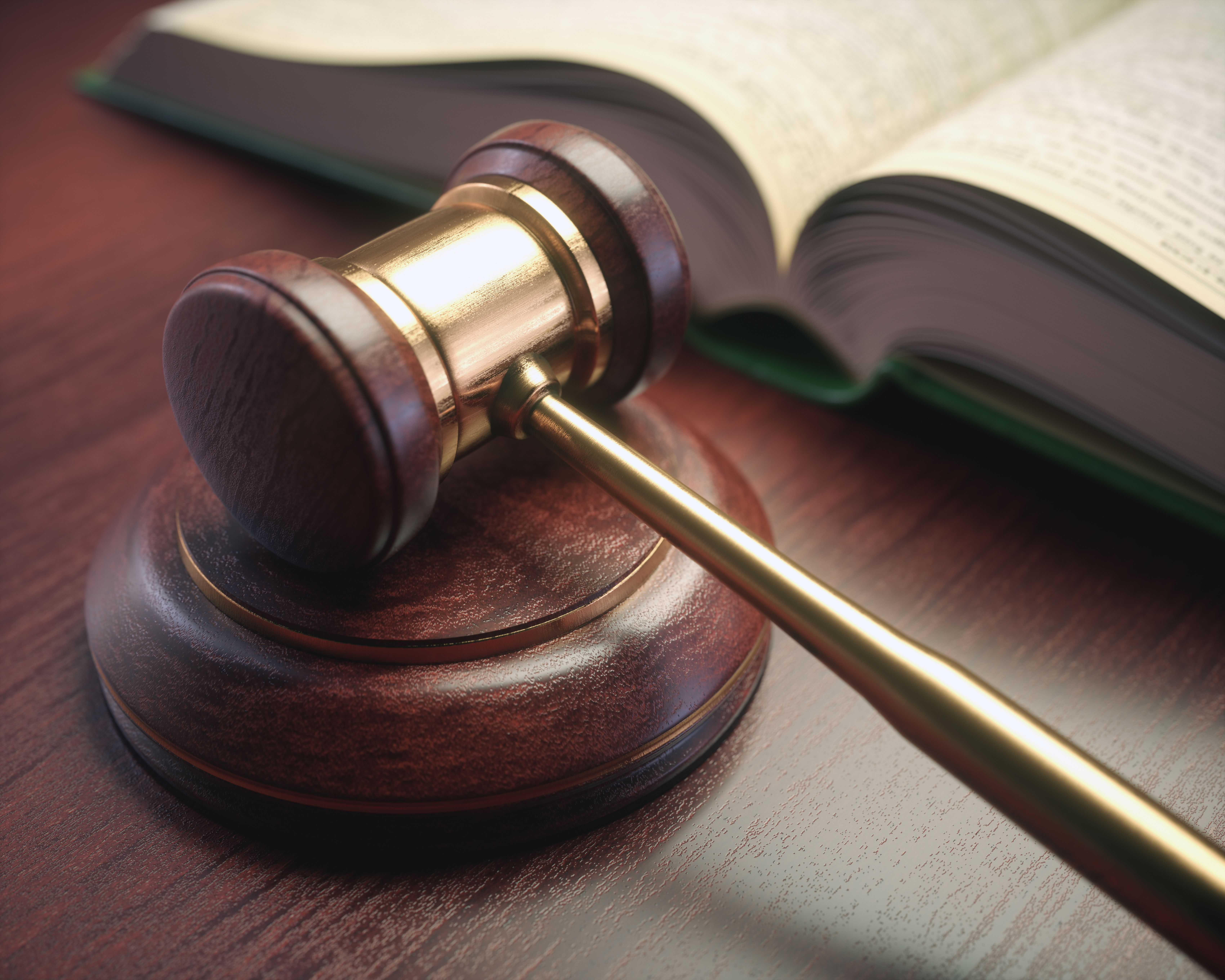 Wooden judge hammer with golden details and a legislation book beside