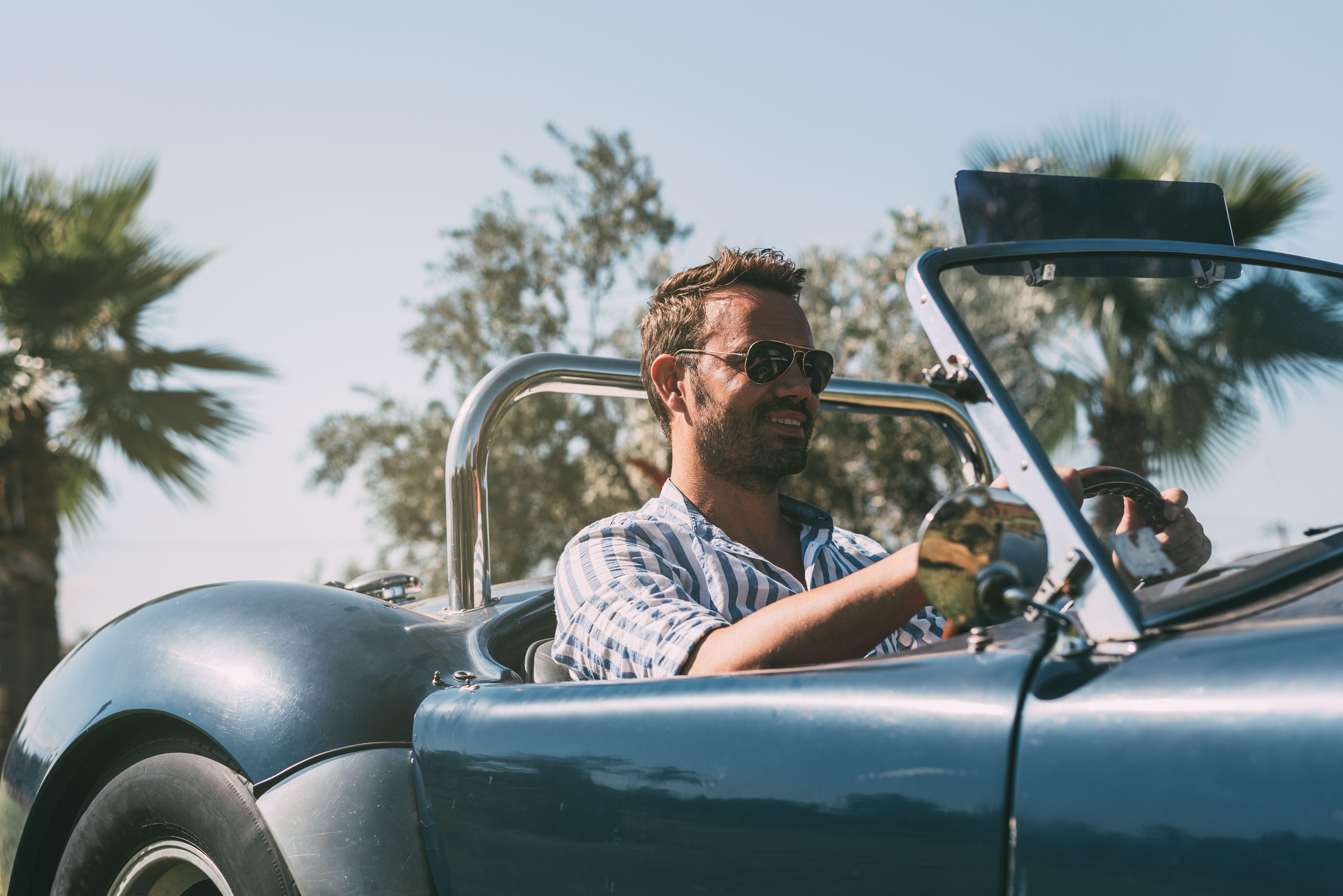 A man driving a convertible car
