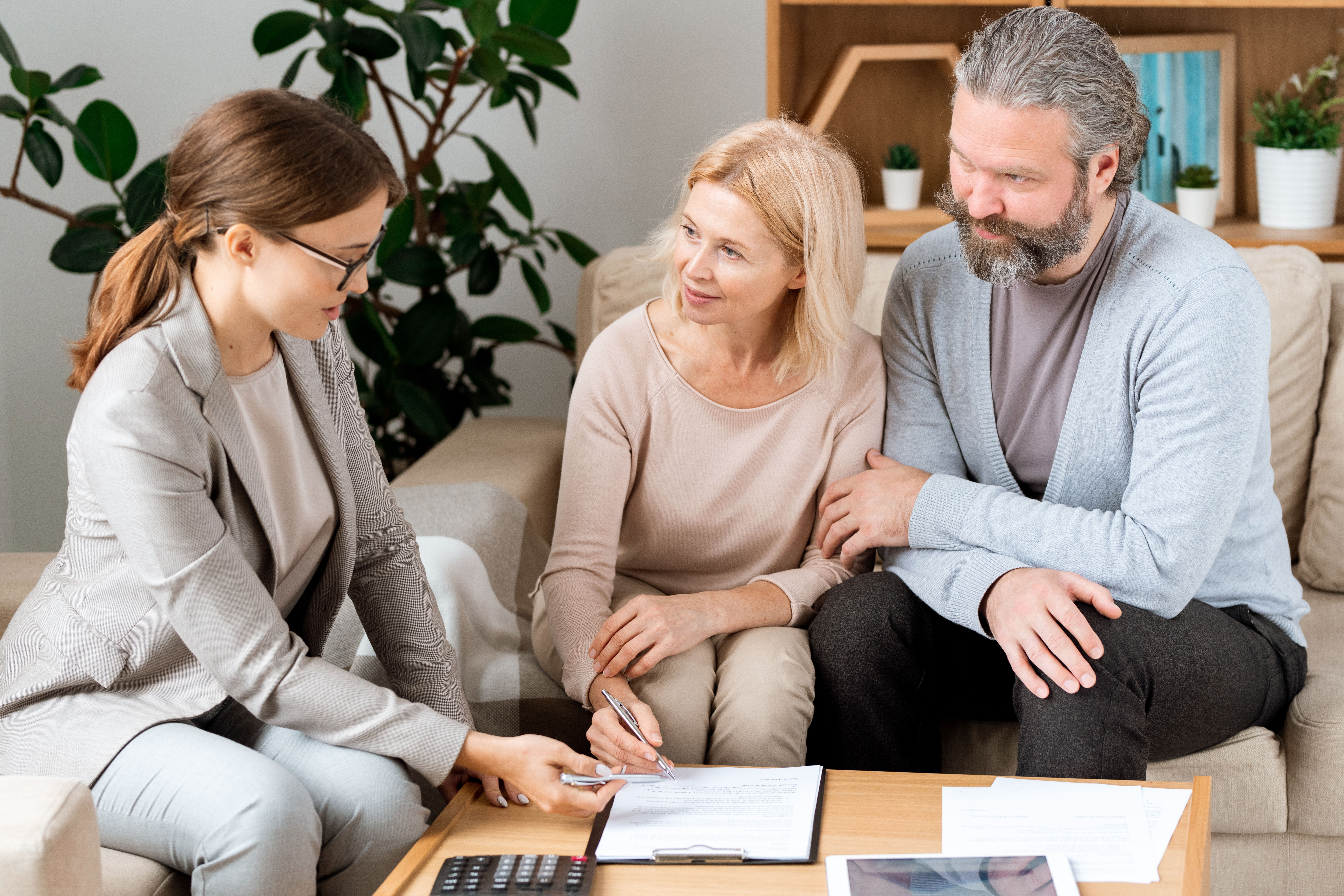 A female real estate and an old couple going through a renewal contract together at a wooden table in a white office with a wooden bookshelf. .JPG