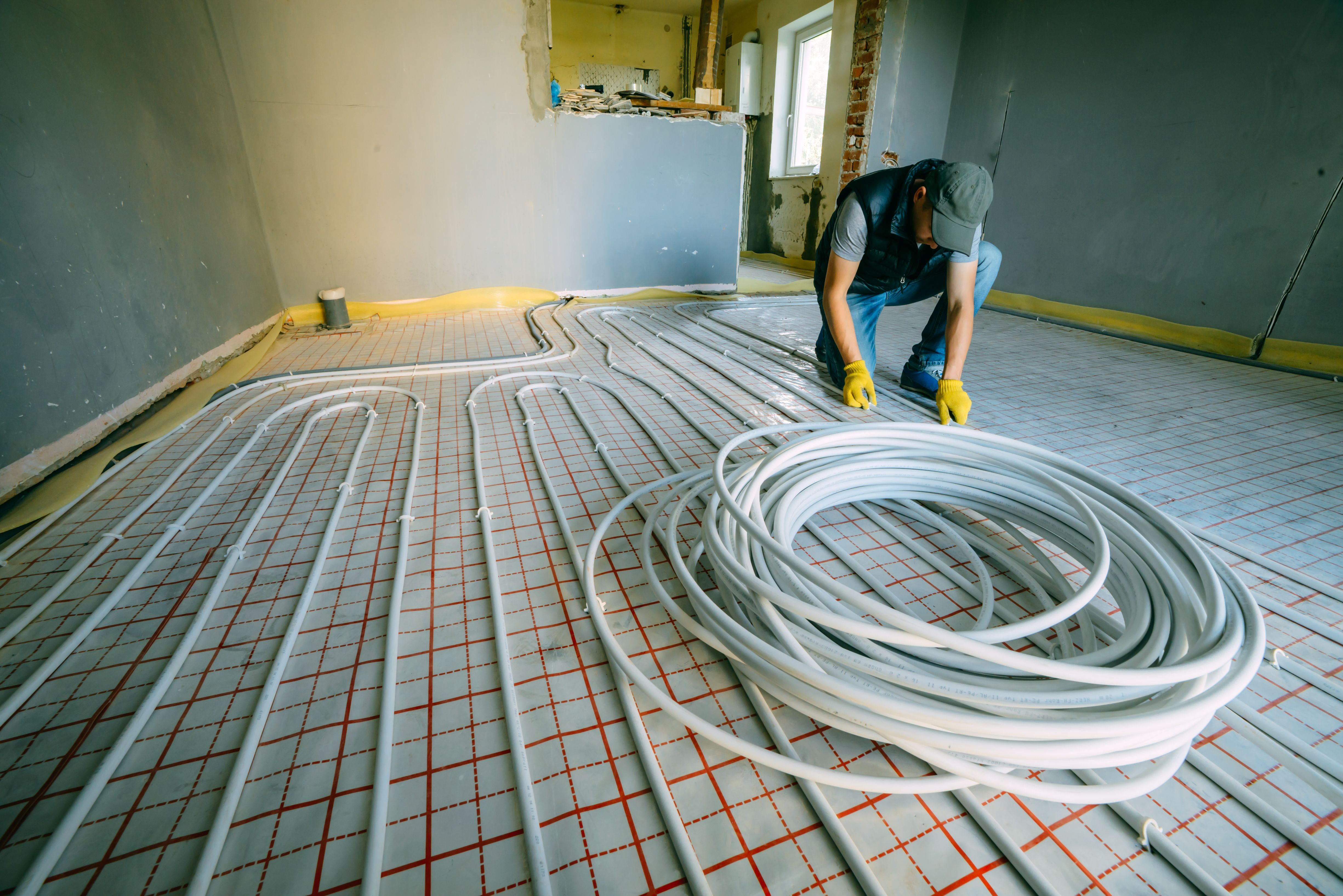 A worker installing pipes for an underfloor heating system in a room with grey walls and a doorway under construction .jpg