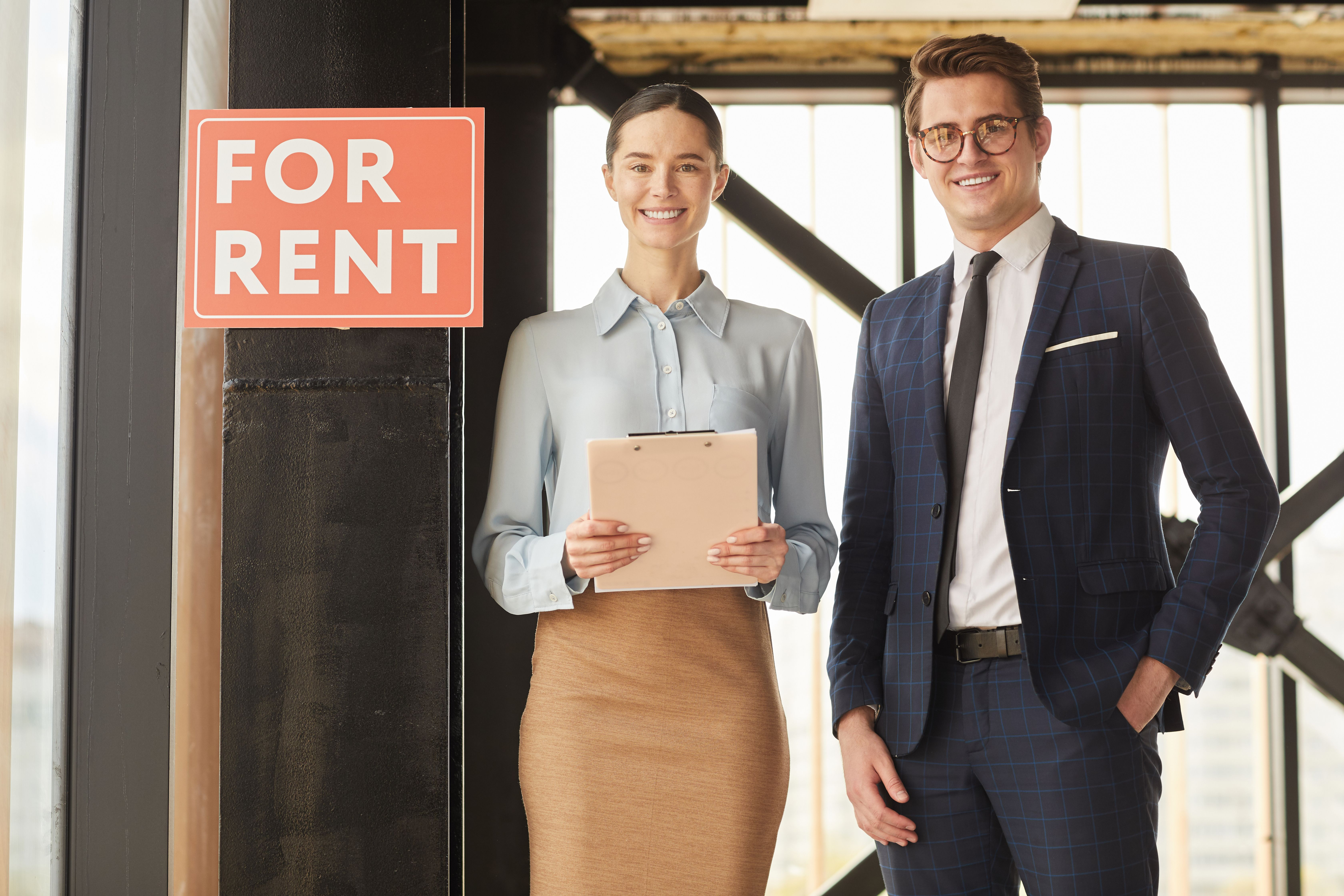 Waist up portrait of two real estate agents smiling at the camera while standing next to a red sign says For Rent