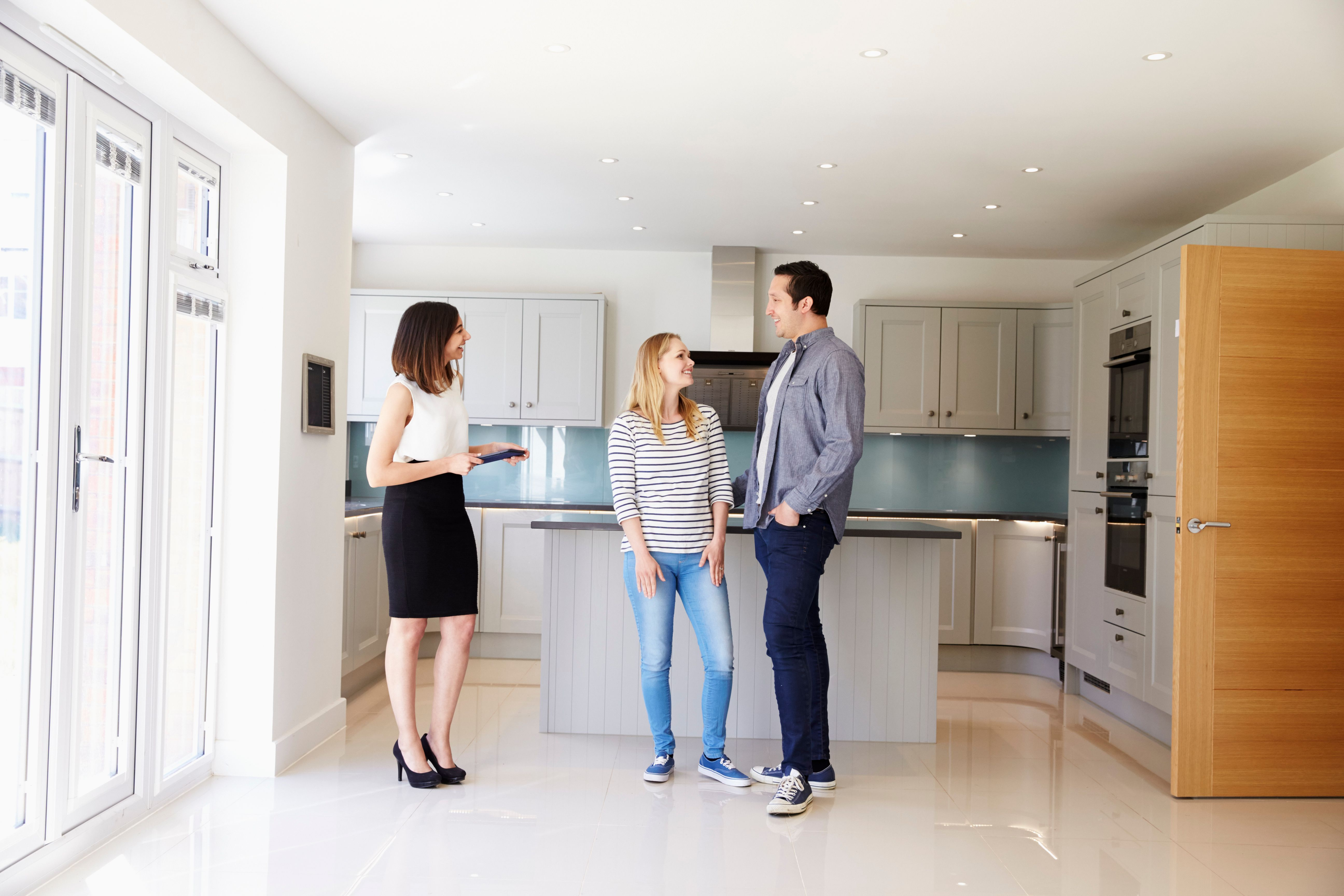 realtor showing young couple around property.jpg