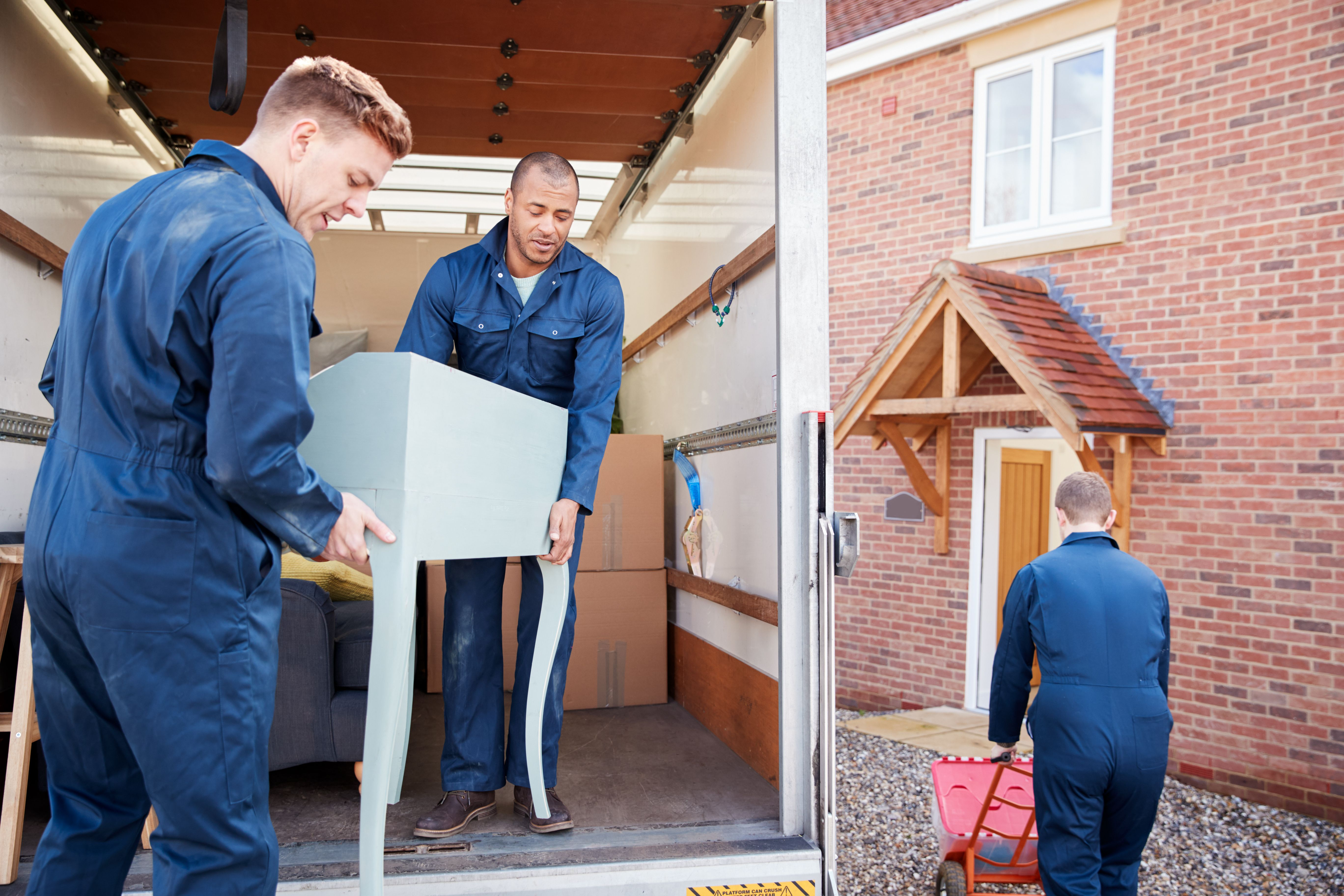 Removals workers unloading furniture and boxes from a truck