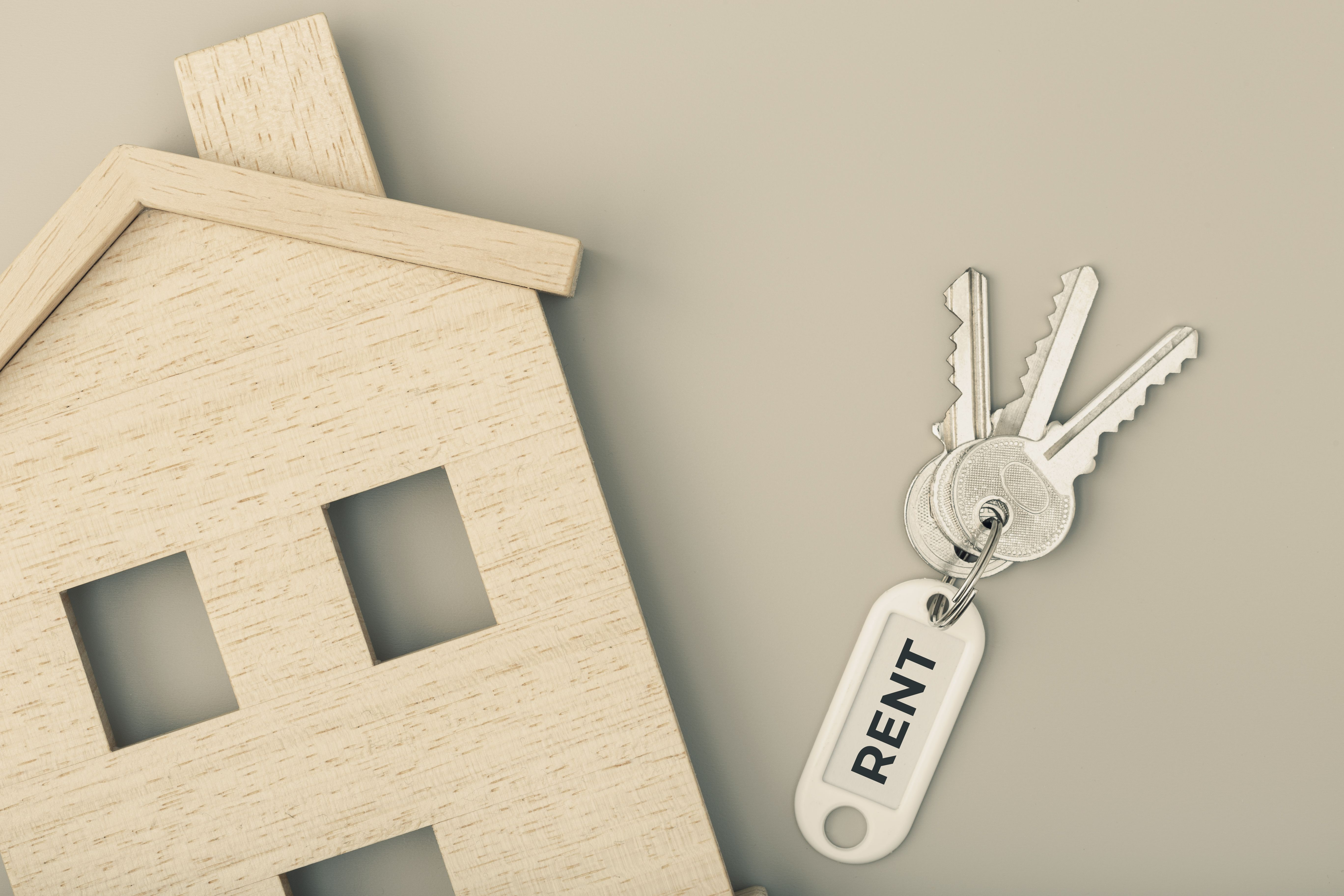 Image concept for renting a house with keys and a model house against a grey background