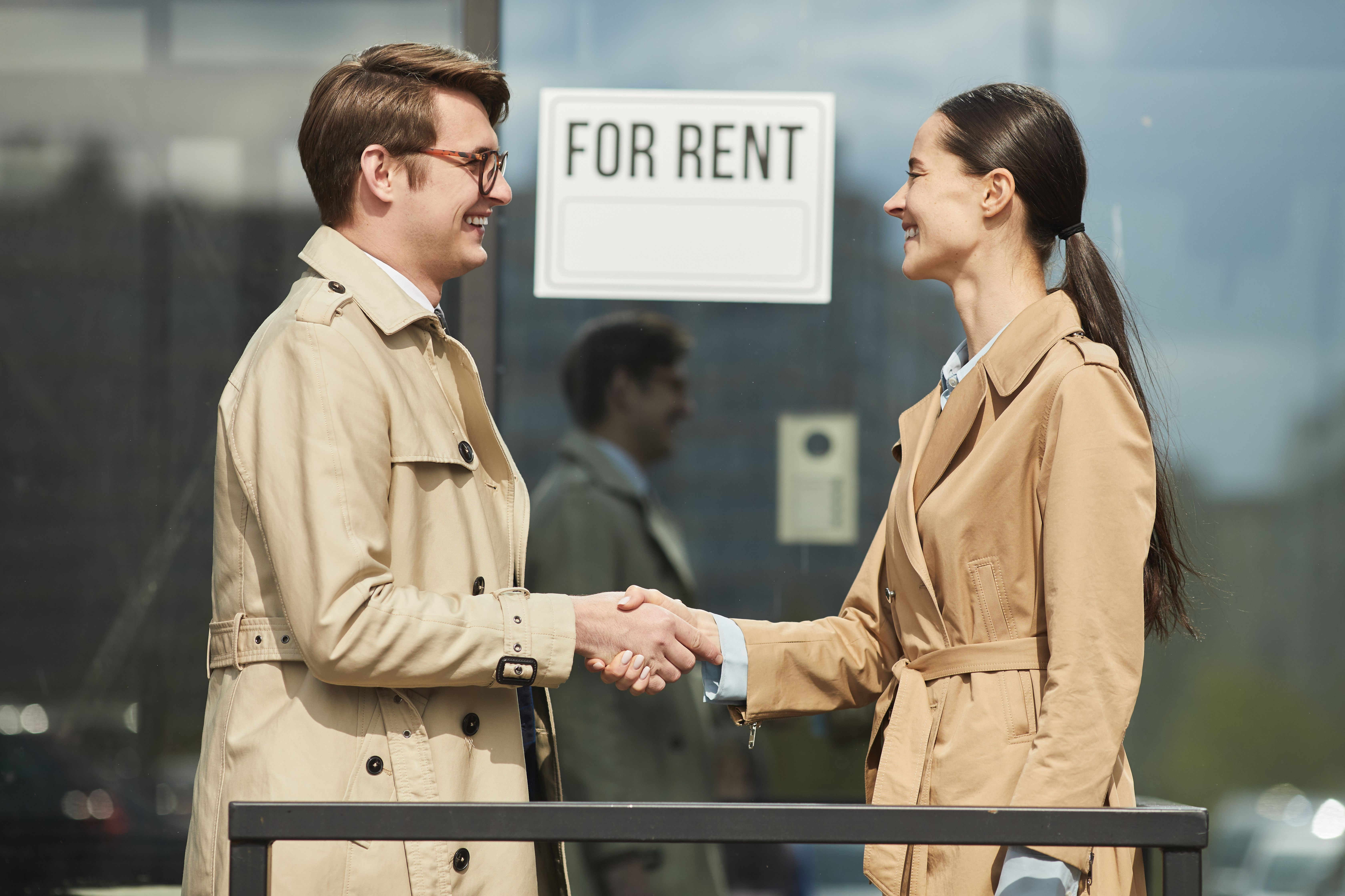 """Side view of a smiling letting agent shaking hands with client outdoors while standing next to """"For rent"""" sign"""