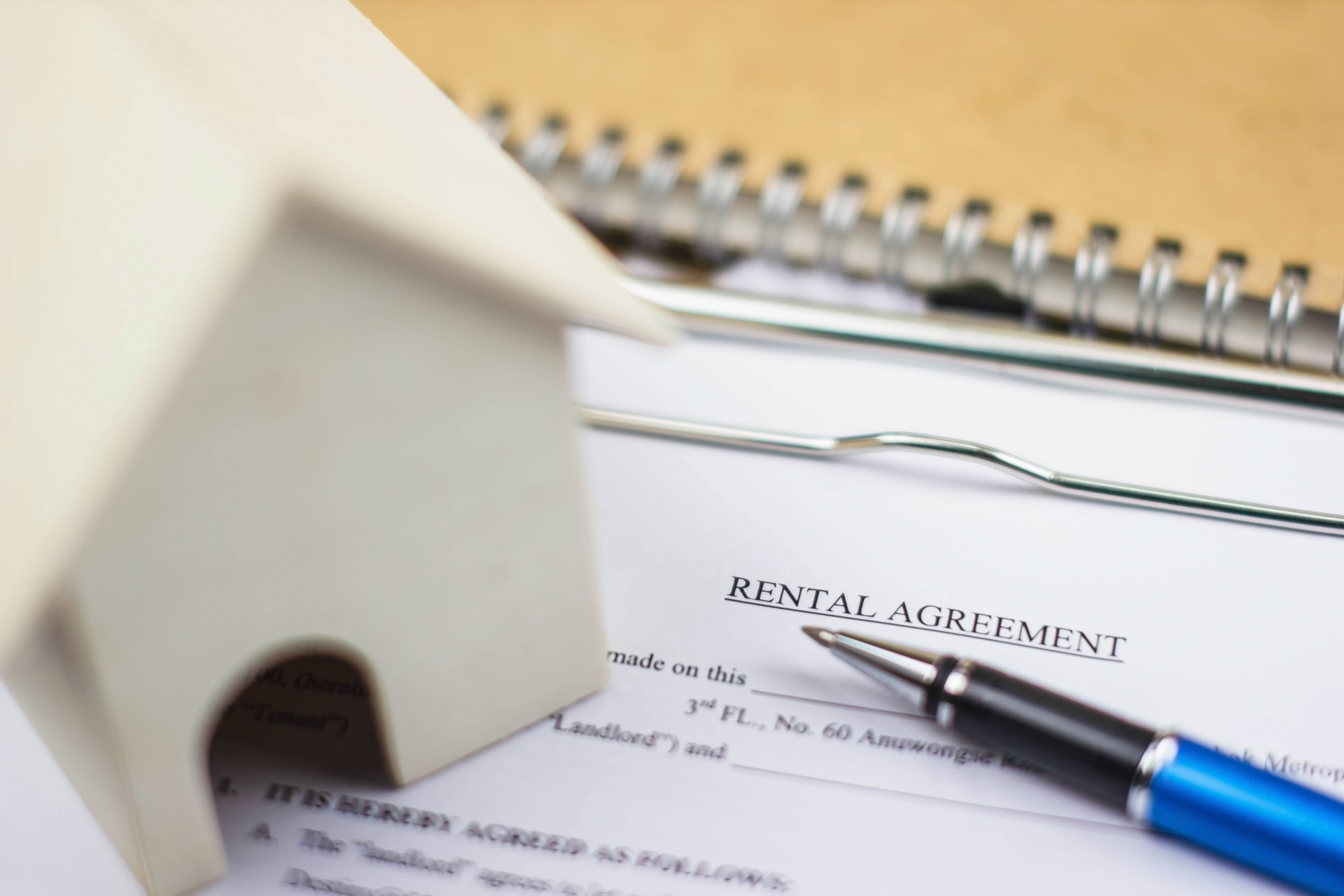A rental agreement underneath a house model contains terms of living and rental cost at a Build To Rent property.