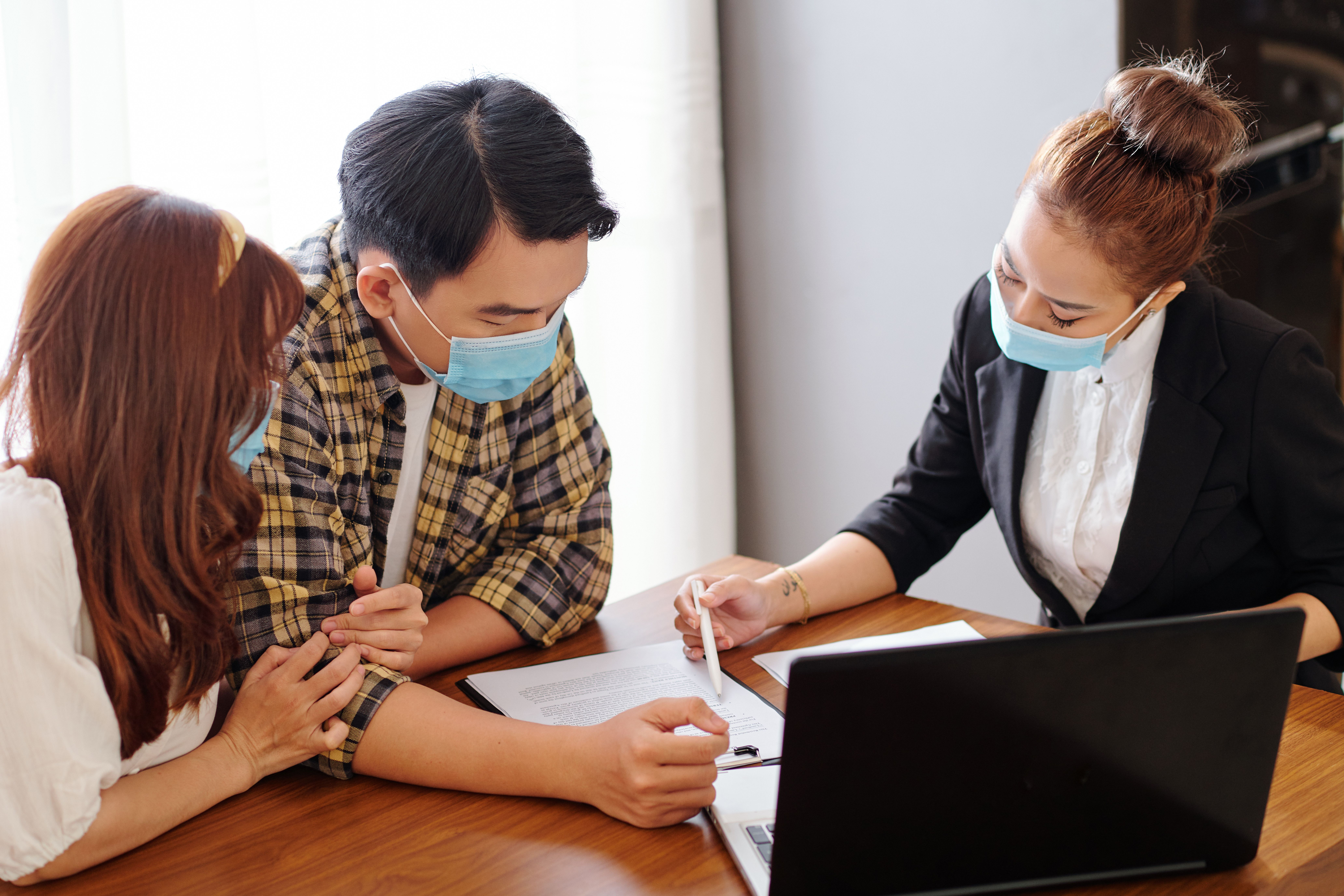A young couple signing an agreement in office of a letting agent