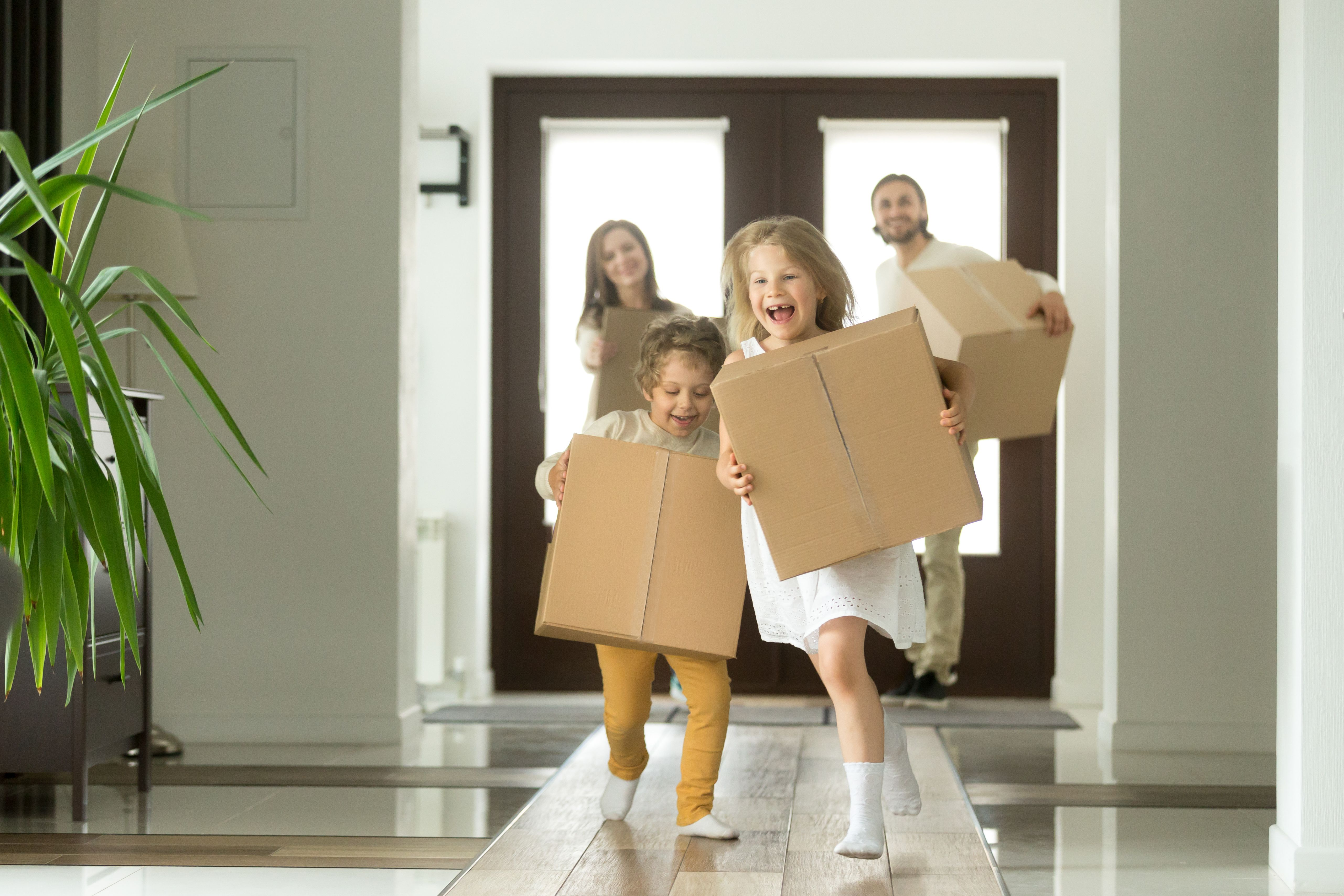 A family of 4 in white clothes holding moving boxes in their arms, running with big smiles into their new Build To Rent homes.