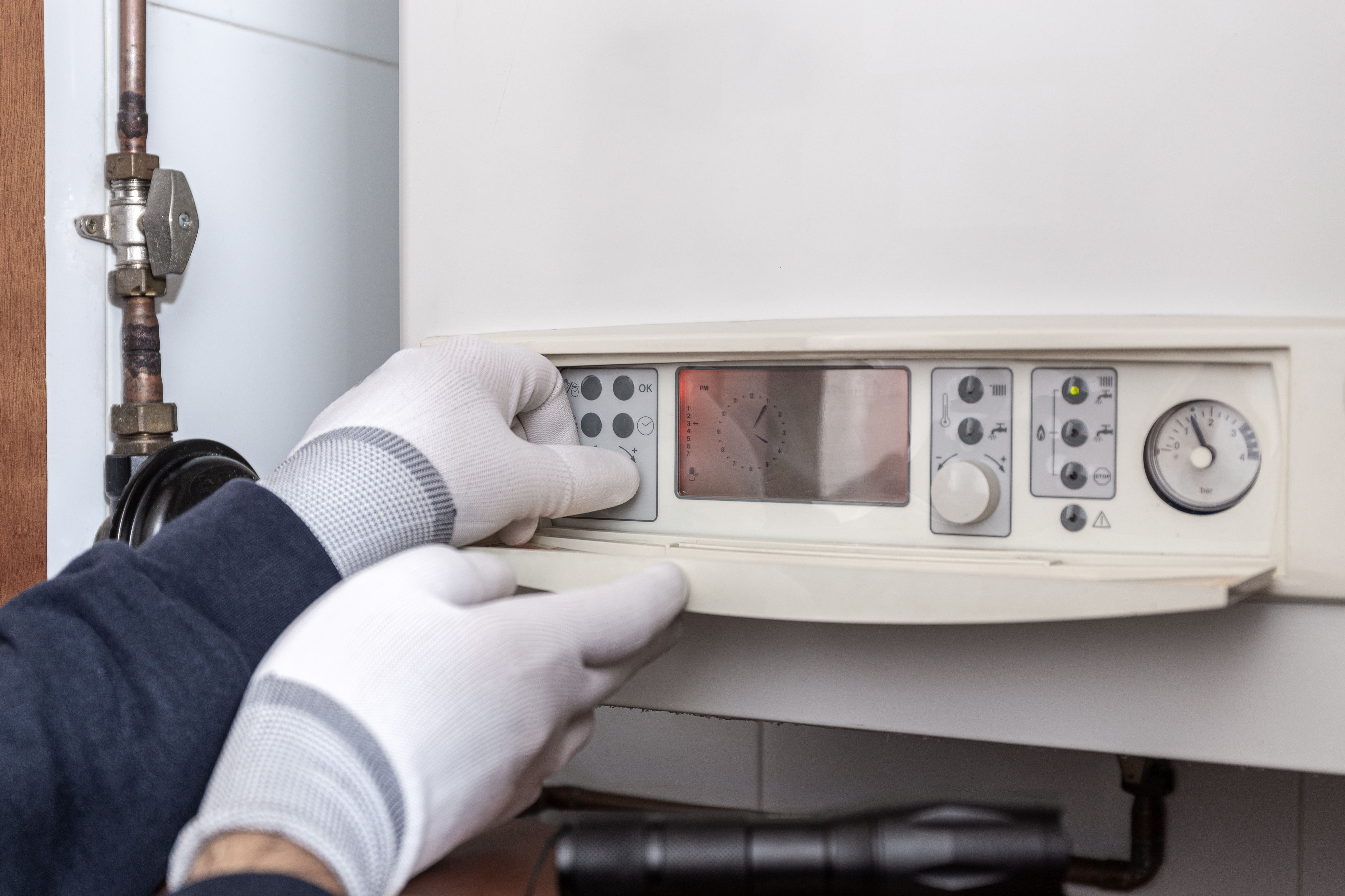 technician servicing heating system in-a house.jpg
