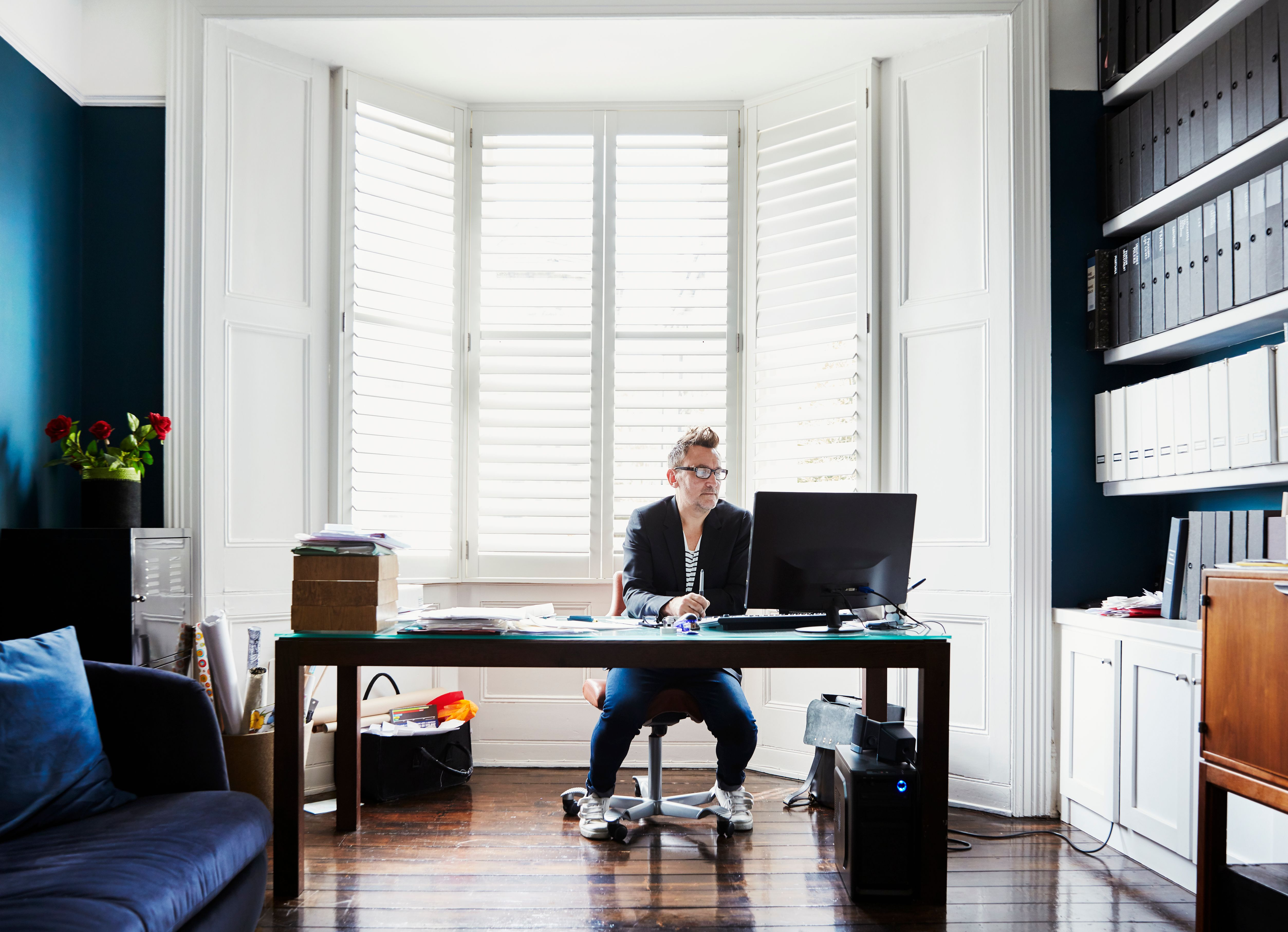 A male tenant sitting at his home office researching about tenancy options available at a Build To Rent property.