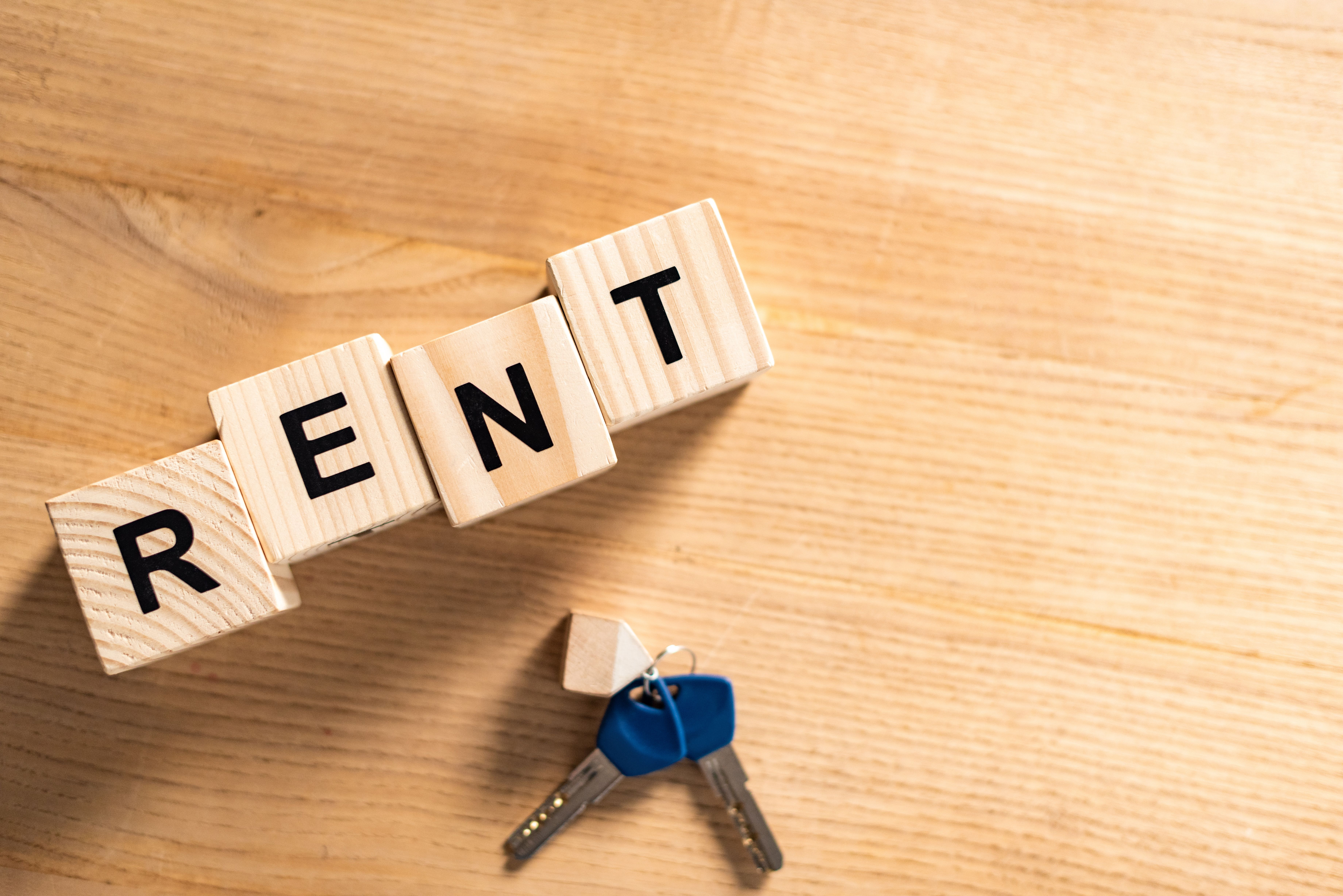 """Top view of a keychain near wooden cubes with """"rent"""" letters on table"""