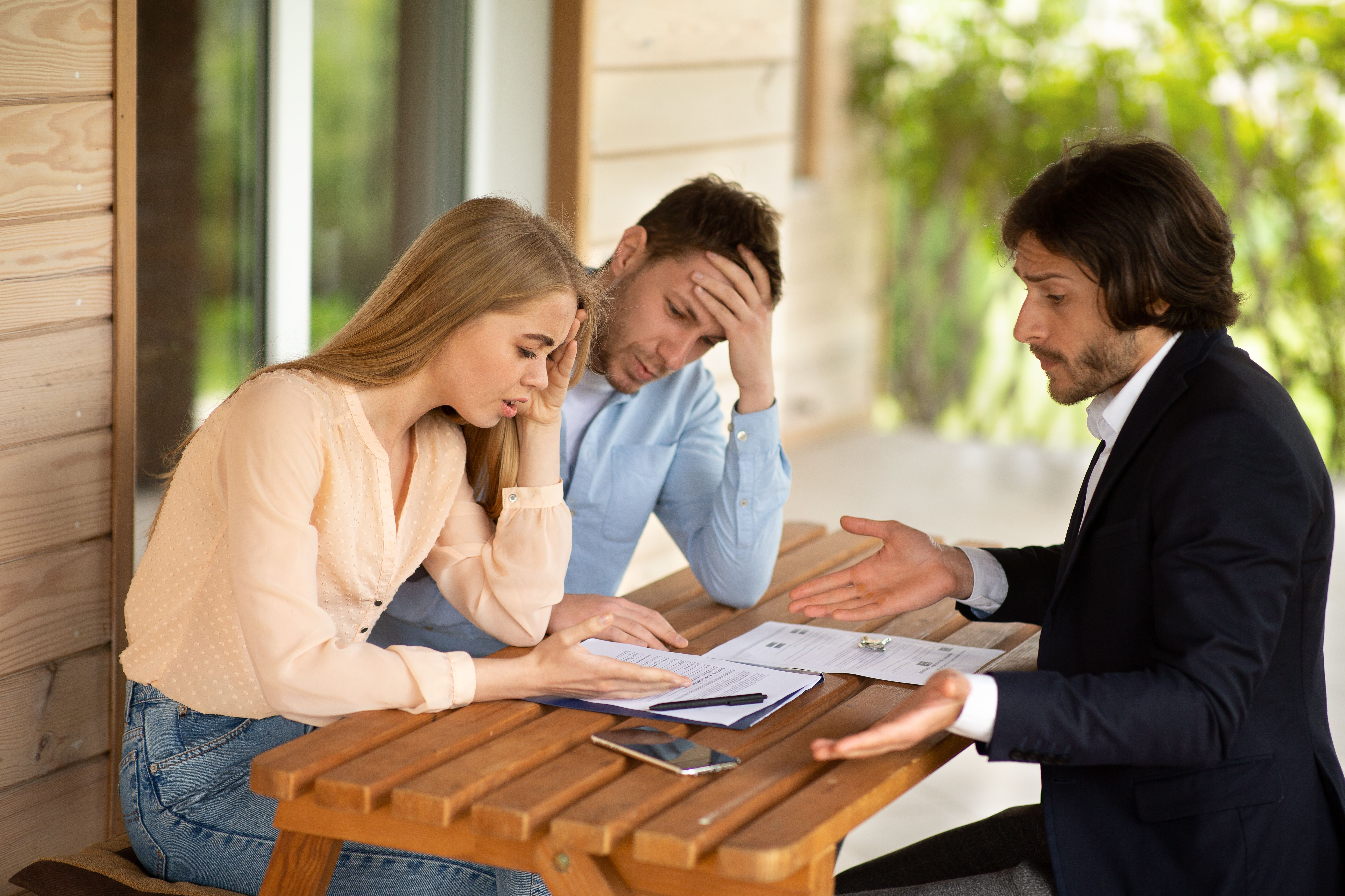A young couple dissatisfied with tenancy agreement terms and a letting agent in front of a house