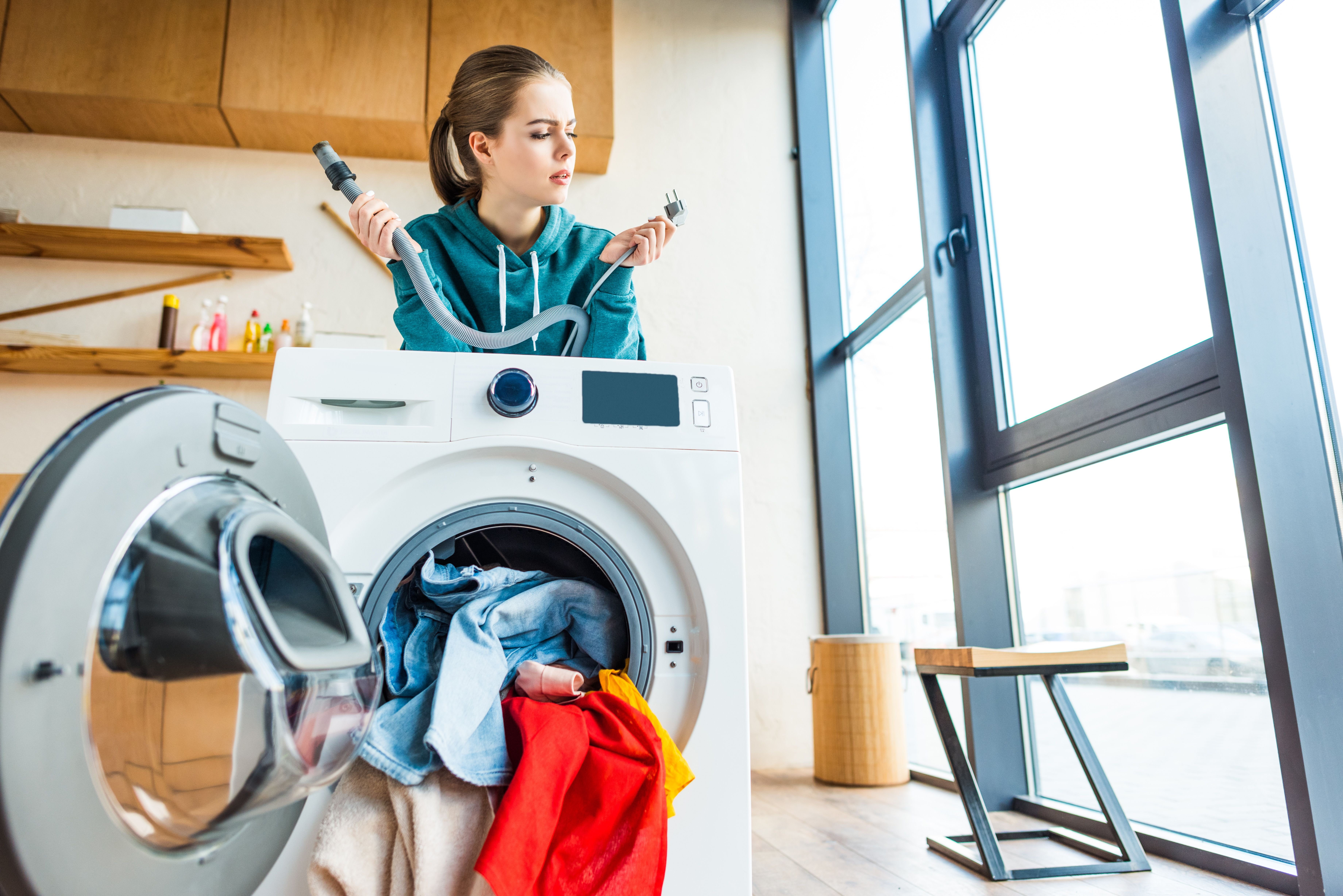 A young woman leaning at a broken washing machine