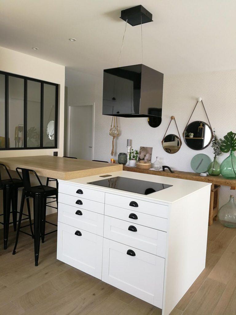 Une table prolonge l'ilot central dans cette cuisine blanche et bois