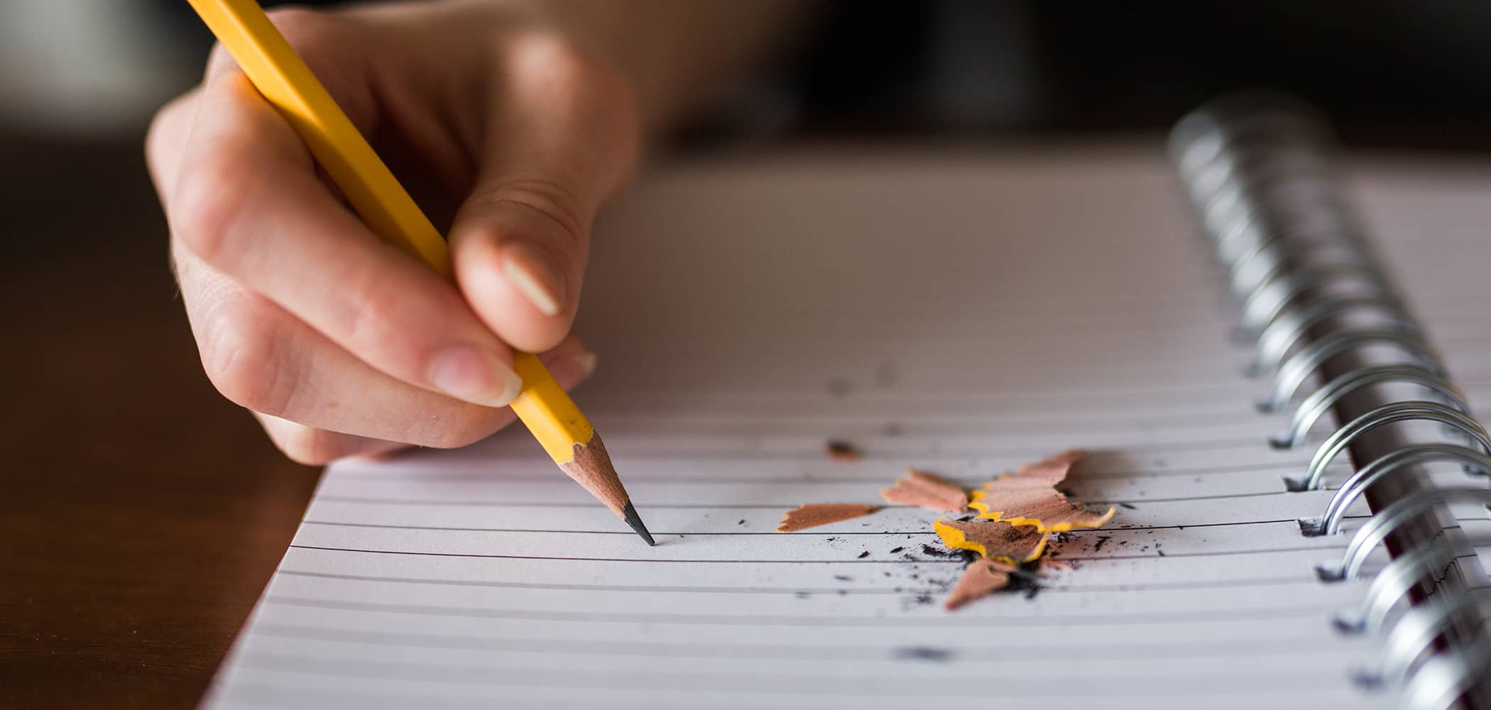 A person writing with a pencil on a notebook