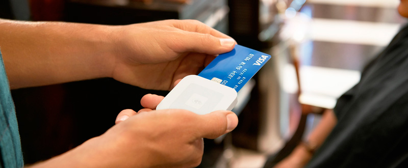 A credit card being read by a Square reader device.