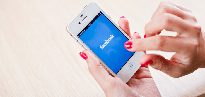 mobile phone in hand with facebook logo