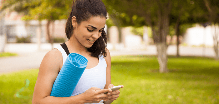 woman with yoga mat and mobile phone