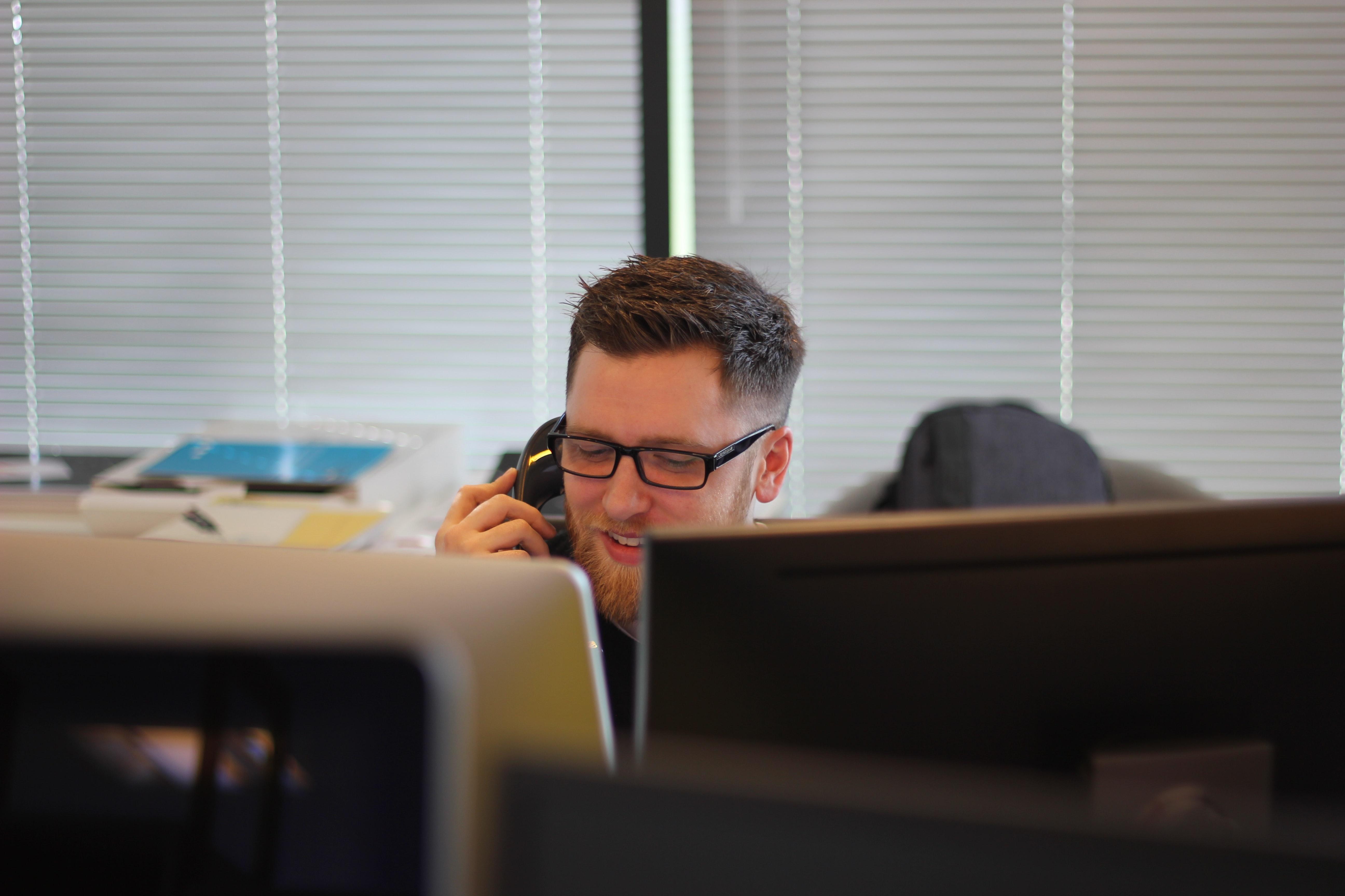 Man on phone behind his computer