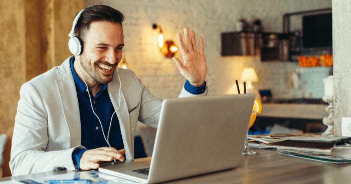 Man waving at an audience using his laptop