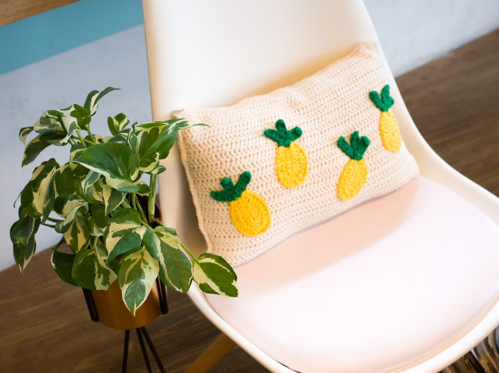 Chaise scandinave design avec un coussin pour plus de confort dans son espace de travail agrémenté d'une plante