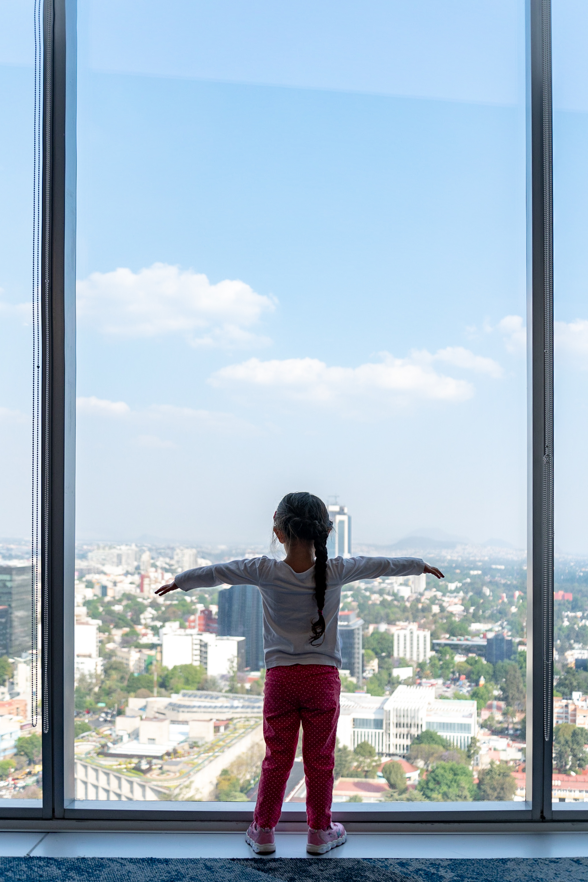 Javier's daughter looking out windown overlooking Mexico City.