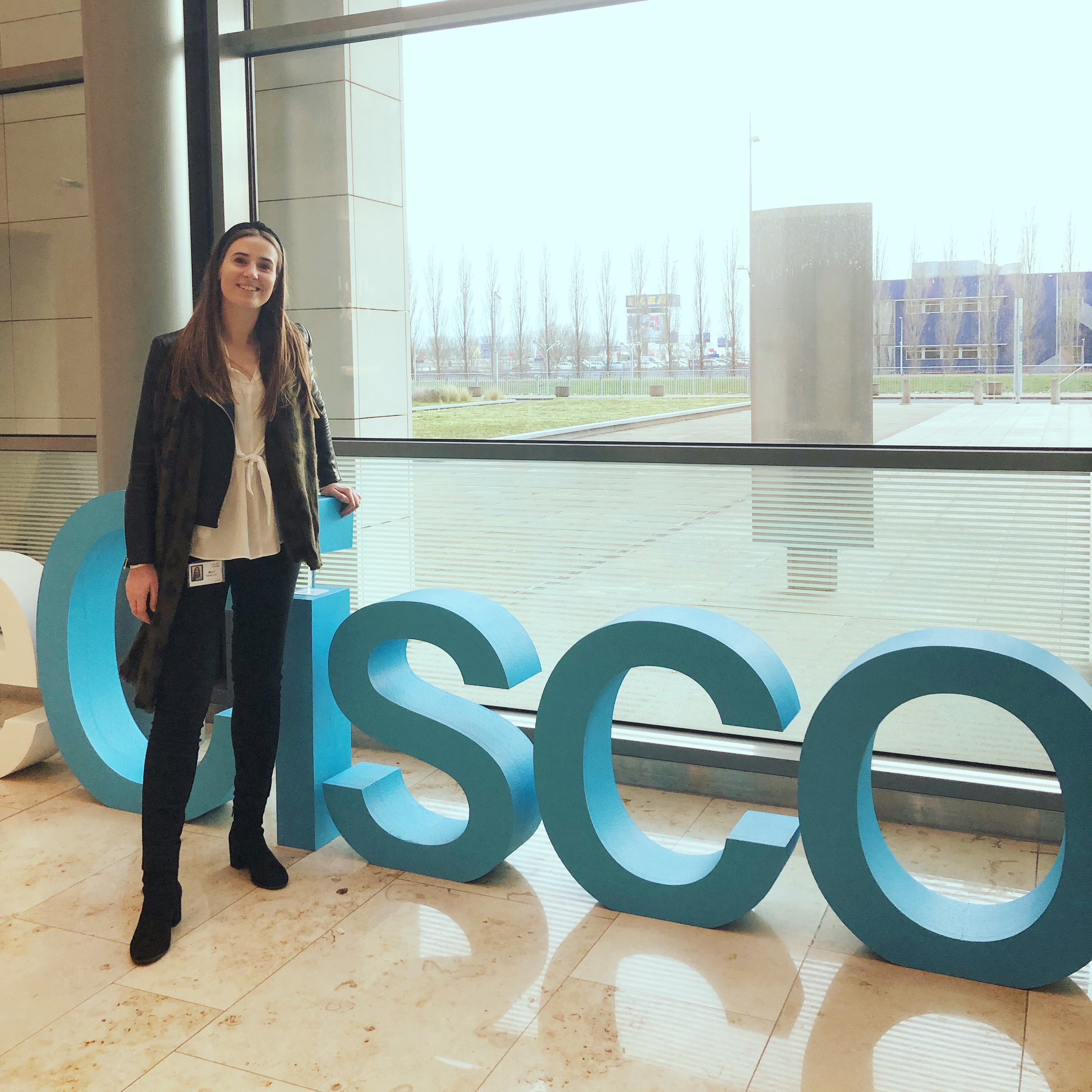 Milly stands in front of 3-D letters spelling out Cisco