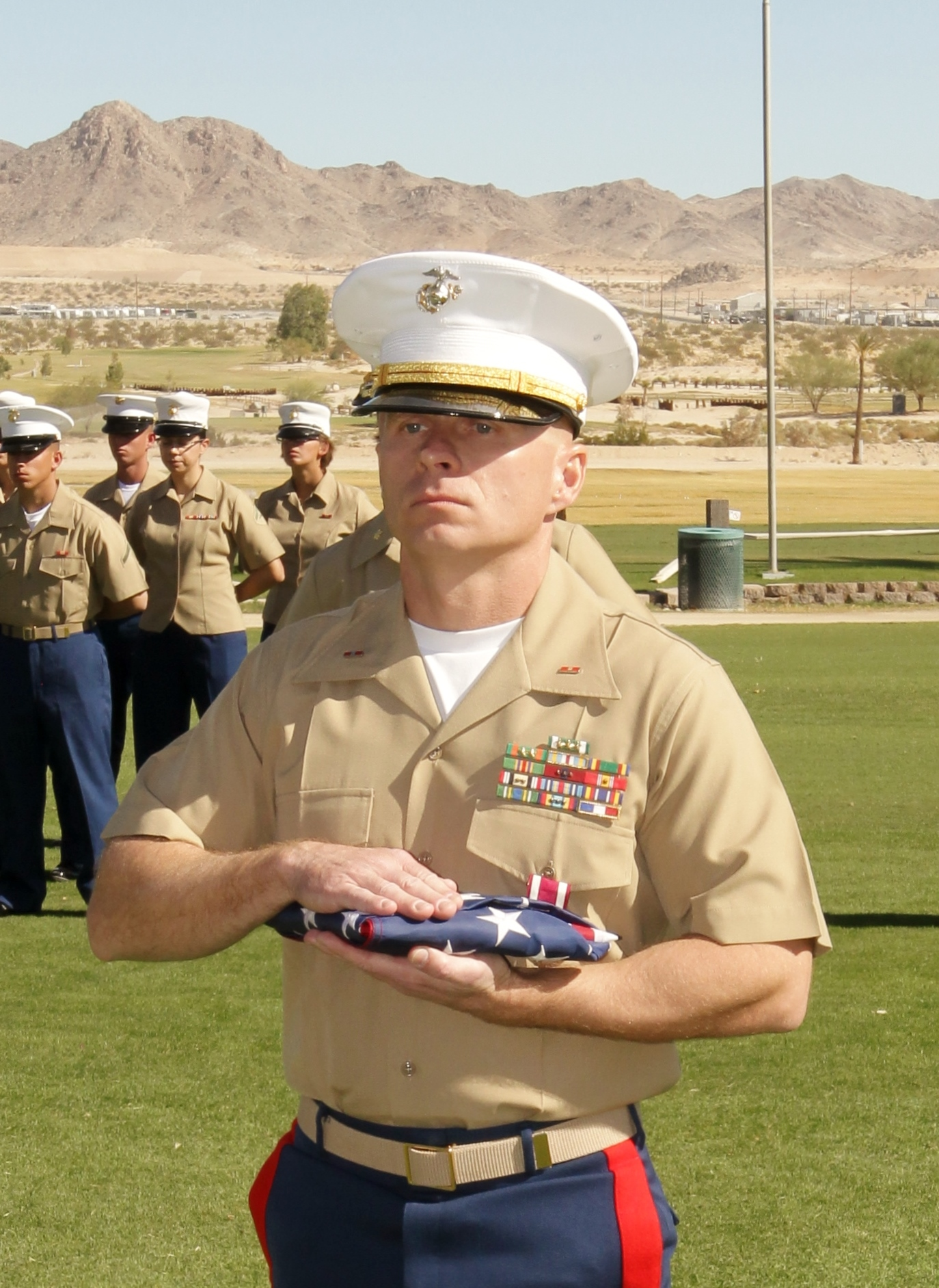 Jon stands in uniform with folded American flag.