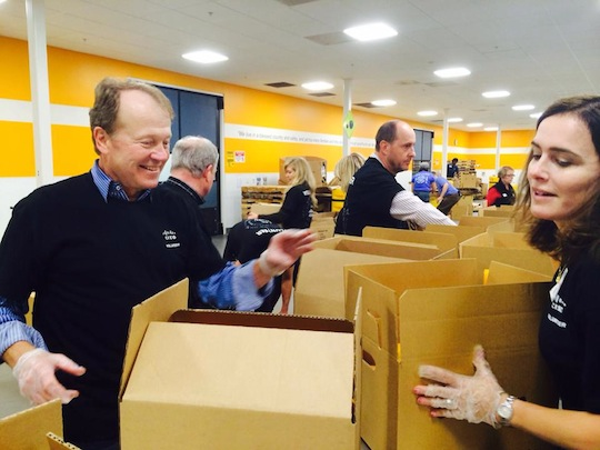 Cisco Chairman and CEO John Chambers sorts food with employee volunteers at the Second Harvest Food Bank of Santa Clara and San Mateo Counties