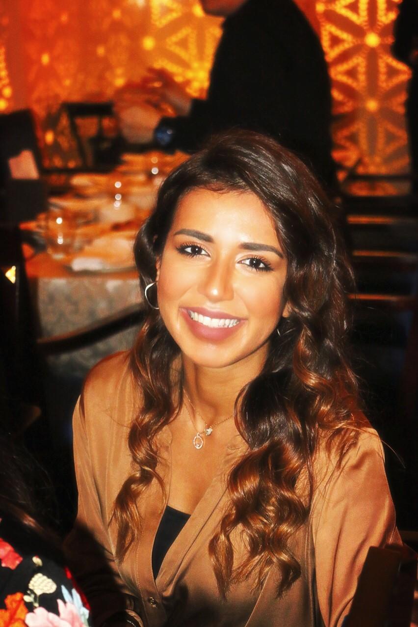 Eman AlTamimi smiling at a dinner.